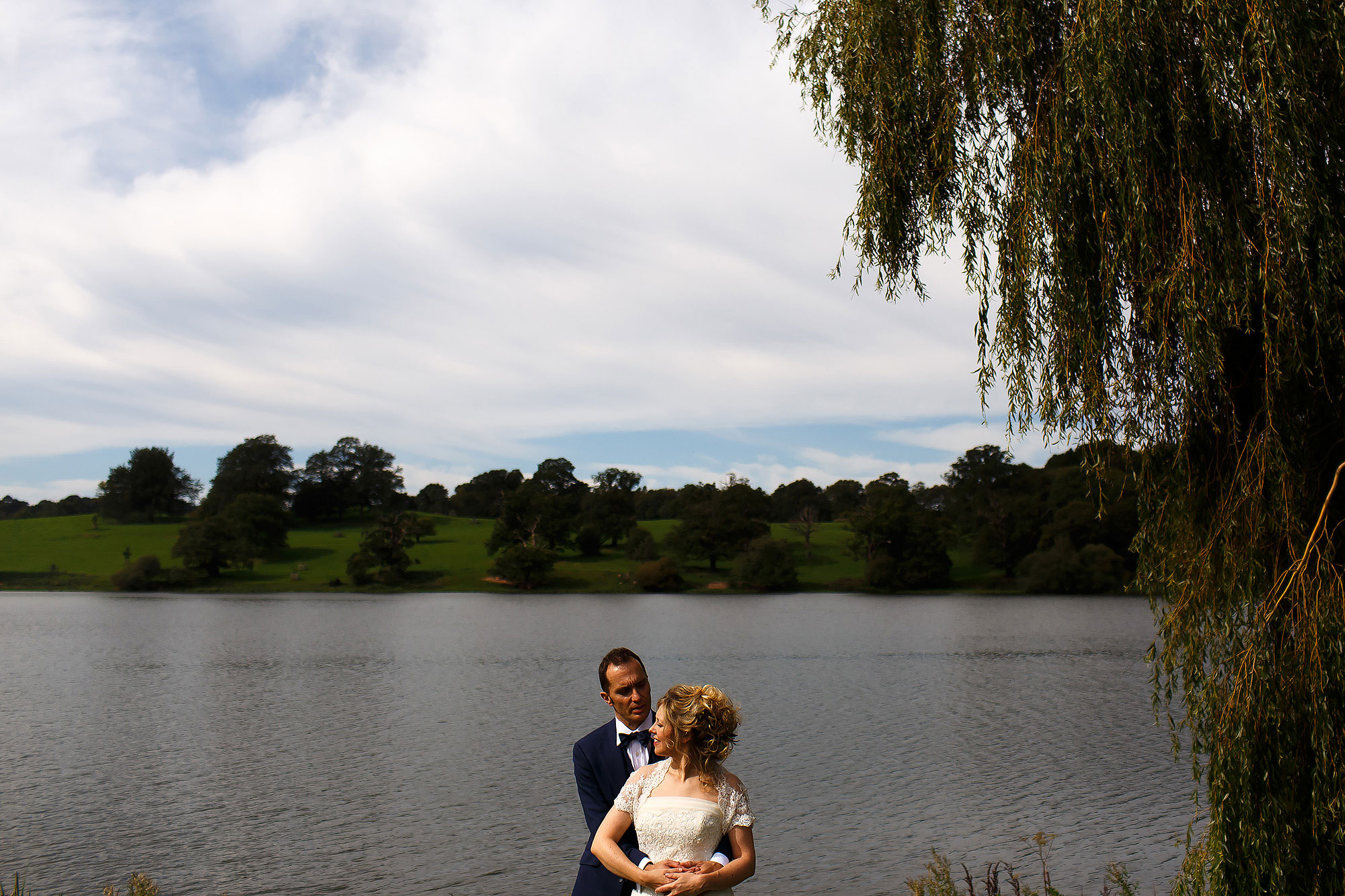 Bride and groom in each others arms on the lakeside at Combermere Abbey
