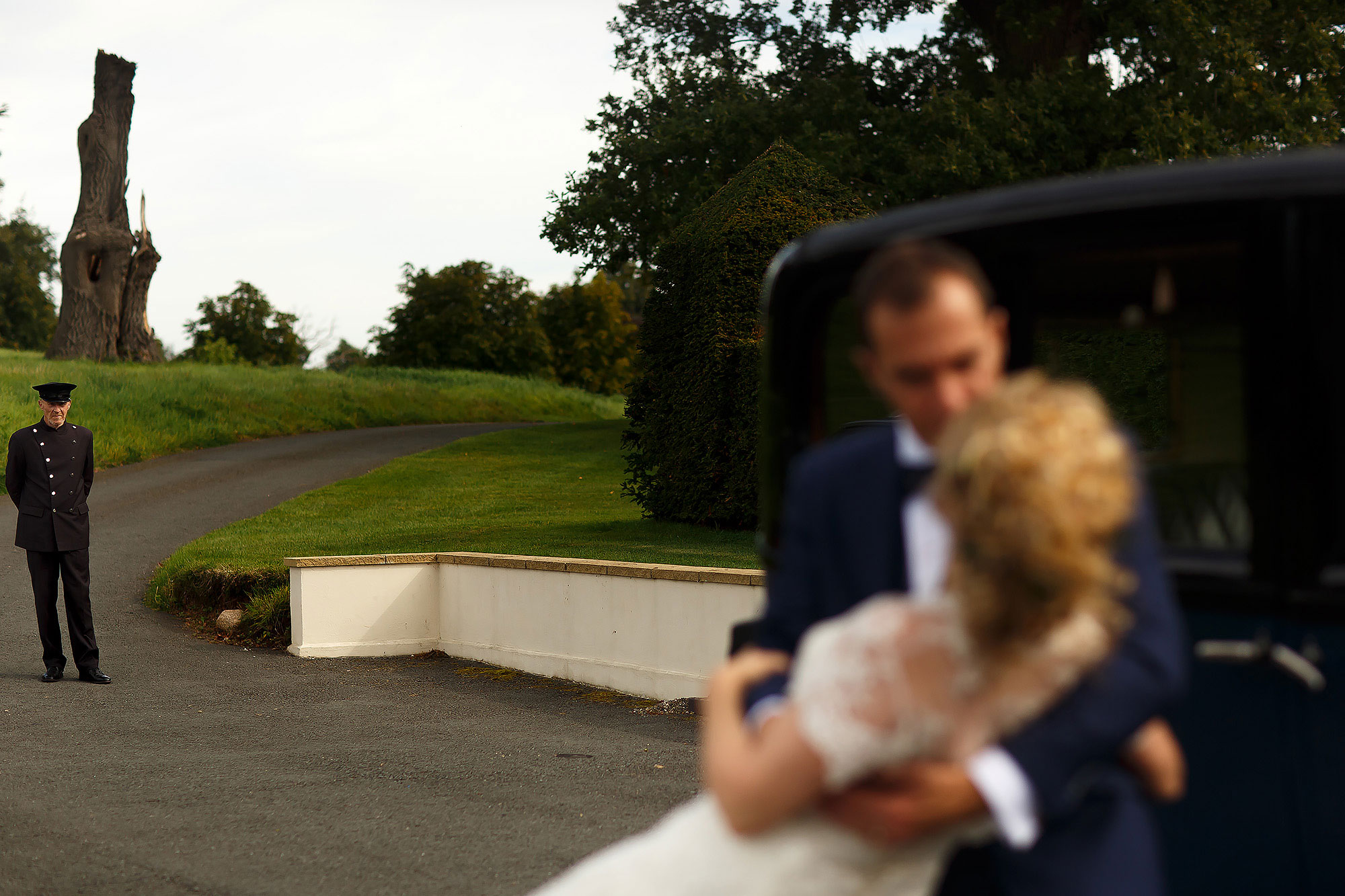 Bride and groom in front of the wedding car at Combermere Abbey as the driver looks on