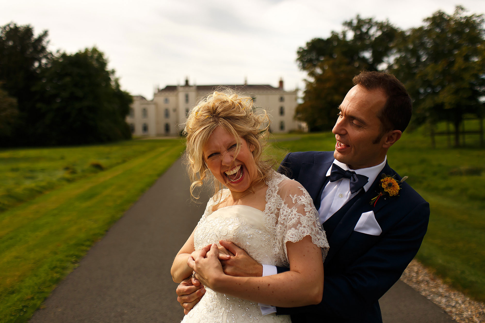 Bride and groom dancing on the drive of Combermere Abbey with the Abbey in the background