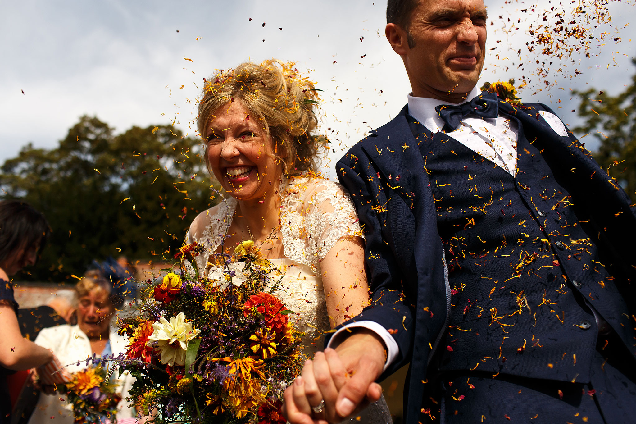 Bride and Groom walking as yellow confetti covers their faces