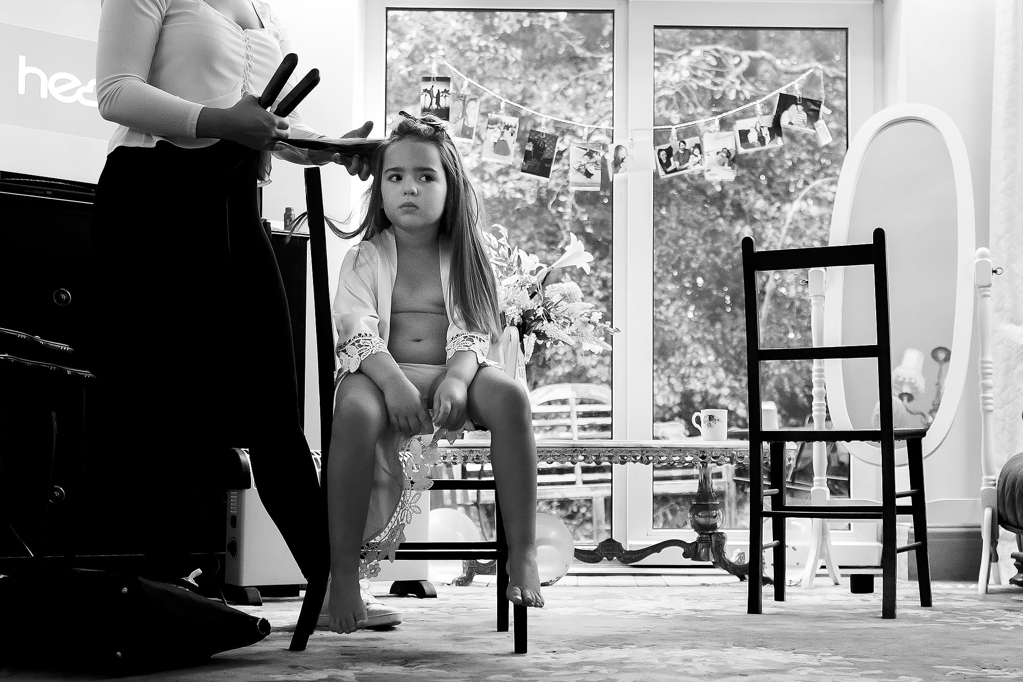Flower girl pulling grumpy face as she sits legs dangling on a chair having hair done on wedding morning | Wellbeing Farm wedding photographs by Toni Darcy Photography
