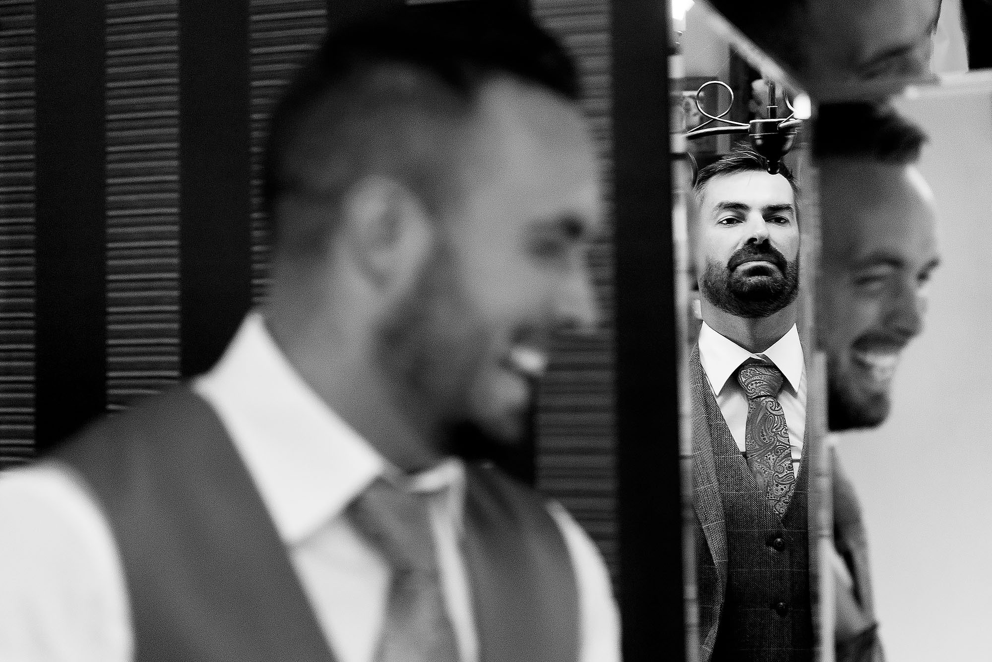 Groom with beard wearing tweed waistcoat and paisley tie looking into mirror on wedding morning | Wellbeing Farm wedding photographs by Toni Darcy Photography