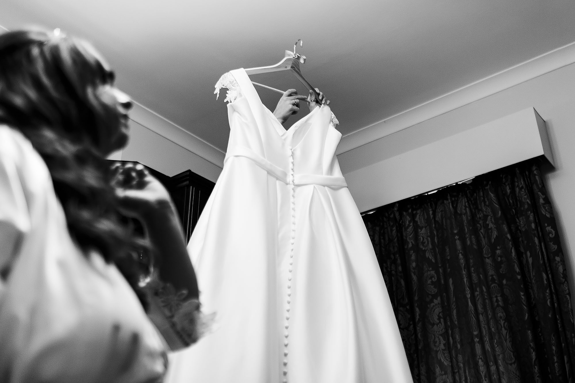Bride looking up as bridesmaid reaches to the top of the wardrobe to lift down wedding dress | Wellbeing Farm wedding photographs by Toni Darcy Photography