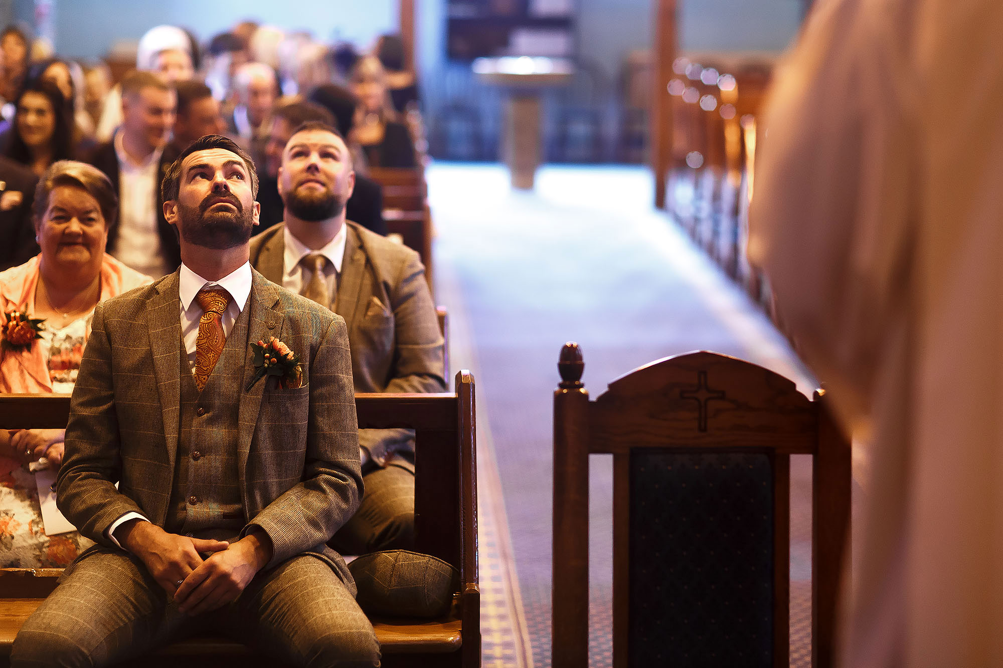 Groom looking nervously upwards as the church is full waiting for the bride to walk down the aisle at St James the Less Rawtenstall | Wellbeing Farm wedding photographs by Toni Darcy Photography