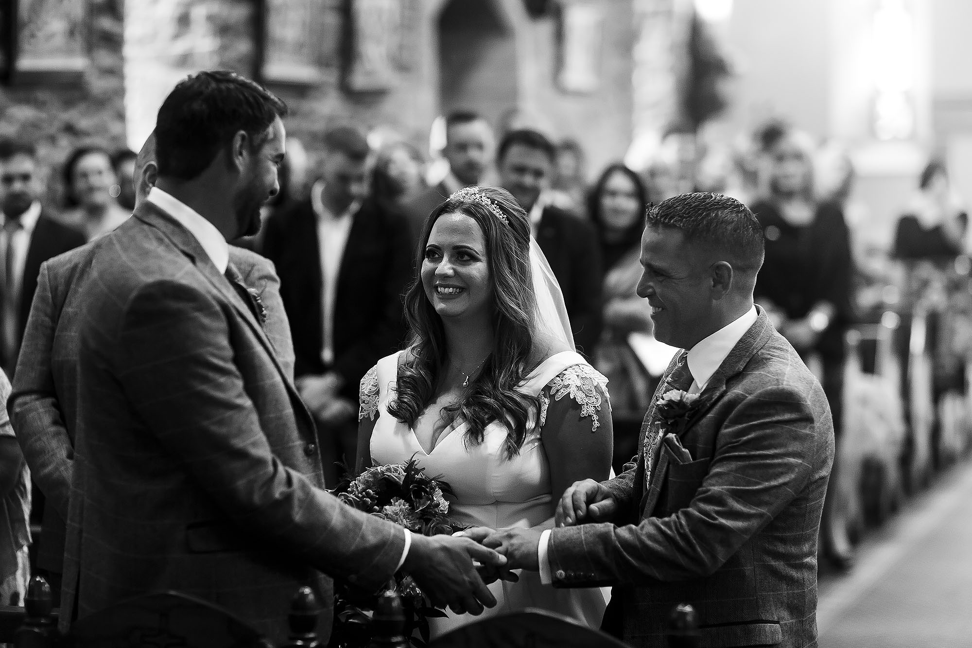 Bride smiling at her groom as her Dad gives her hand away at the top of the aisle at St James the Less | Wellbeing Farm wedding photographs by Toni Darcy Photography