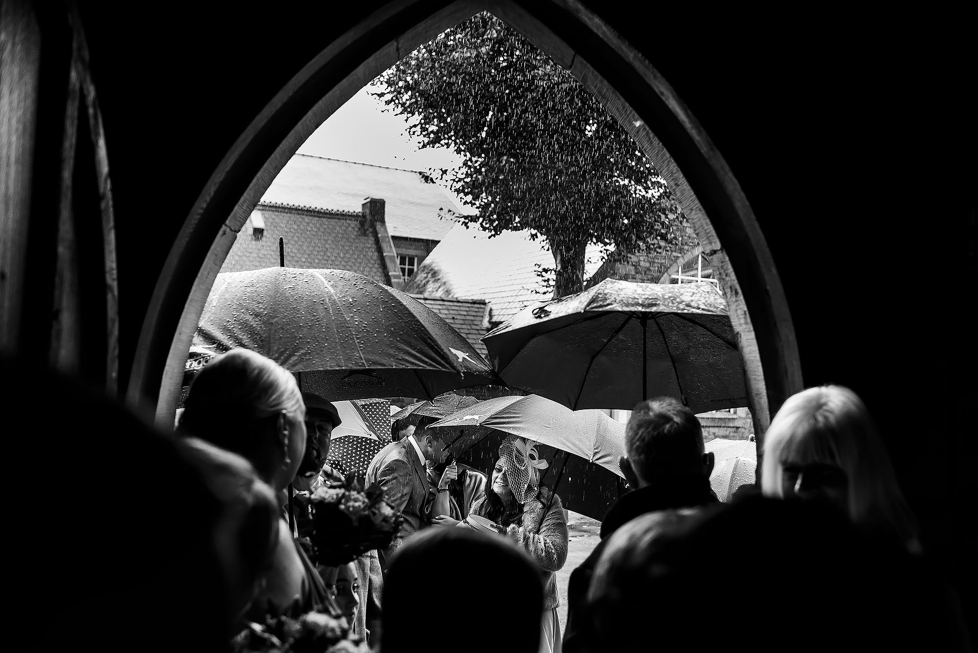 Wedding guests shielding from the rain outside St James the Less Rawtenstall | Wellbeing Farm wedding photographs by Toni Darcy Photography