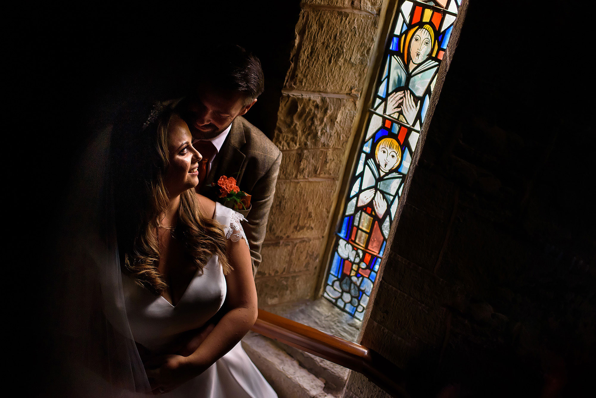 Groom holding bride in his arms close to stained glass window in beautiful light at St James the Less | Wellbeing Farm wedding photographs by Toni Darcy Photography