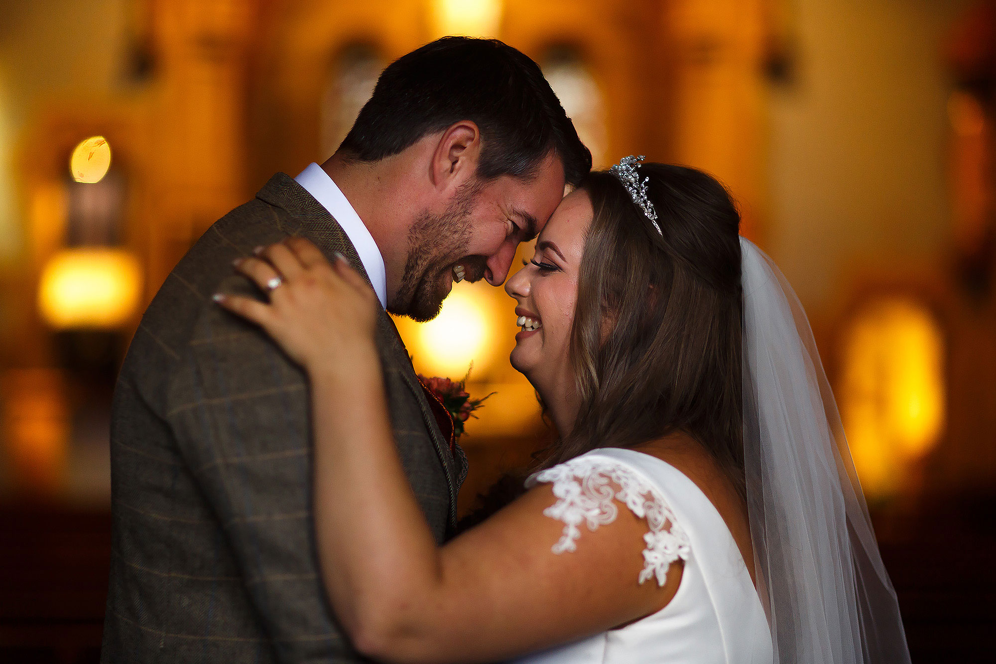 Bride with brunette hair and capped sleeved wedding dress touching forehead with her tall groom inside church with warm lights and candles behind | Wellbeing Farm wedding photographs by Toni Darcy Photography
