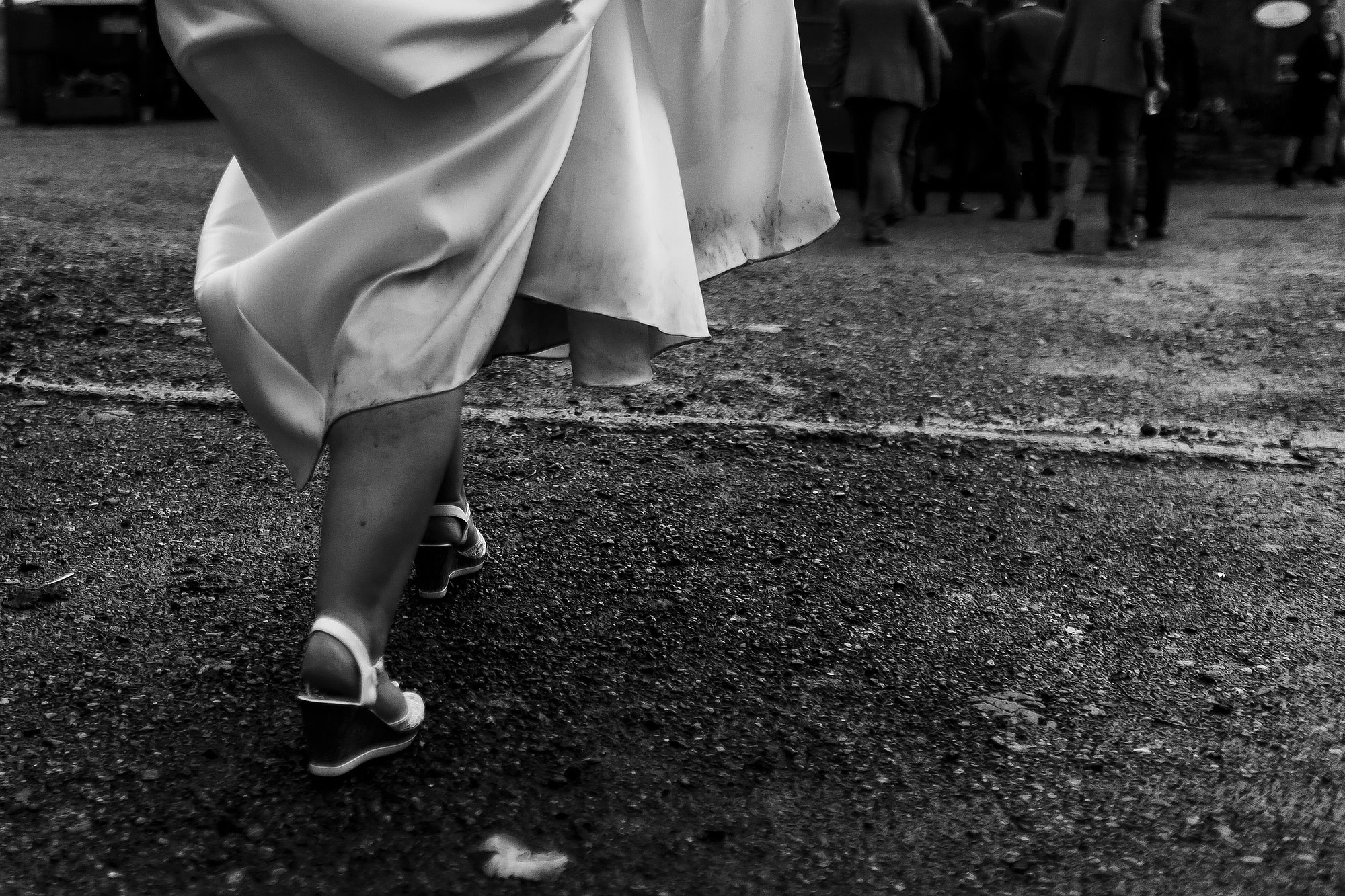 Bride holding dress high showing dirt and rain down the leg as she walks to wedding reception at Wellbeing Farm | Wellbeing Farm wedding photographs by Toni Darcy Photography