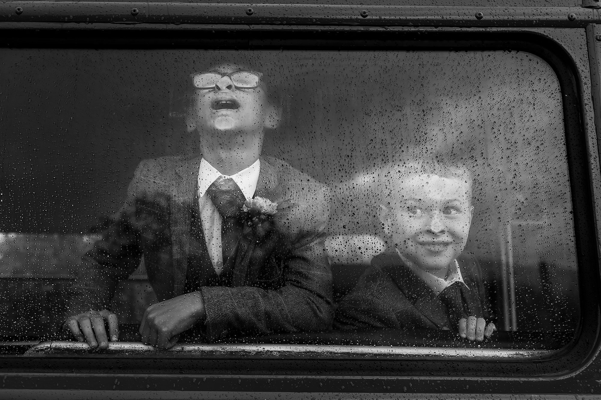 Page Boys pulling faces against the wedding bus window | Wellbeing Farm wedding photographs by Toni Darcy Photography