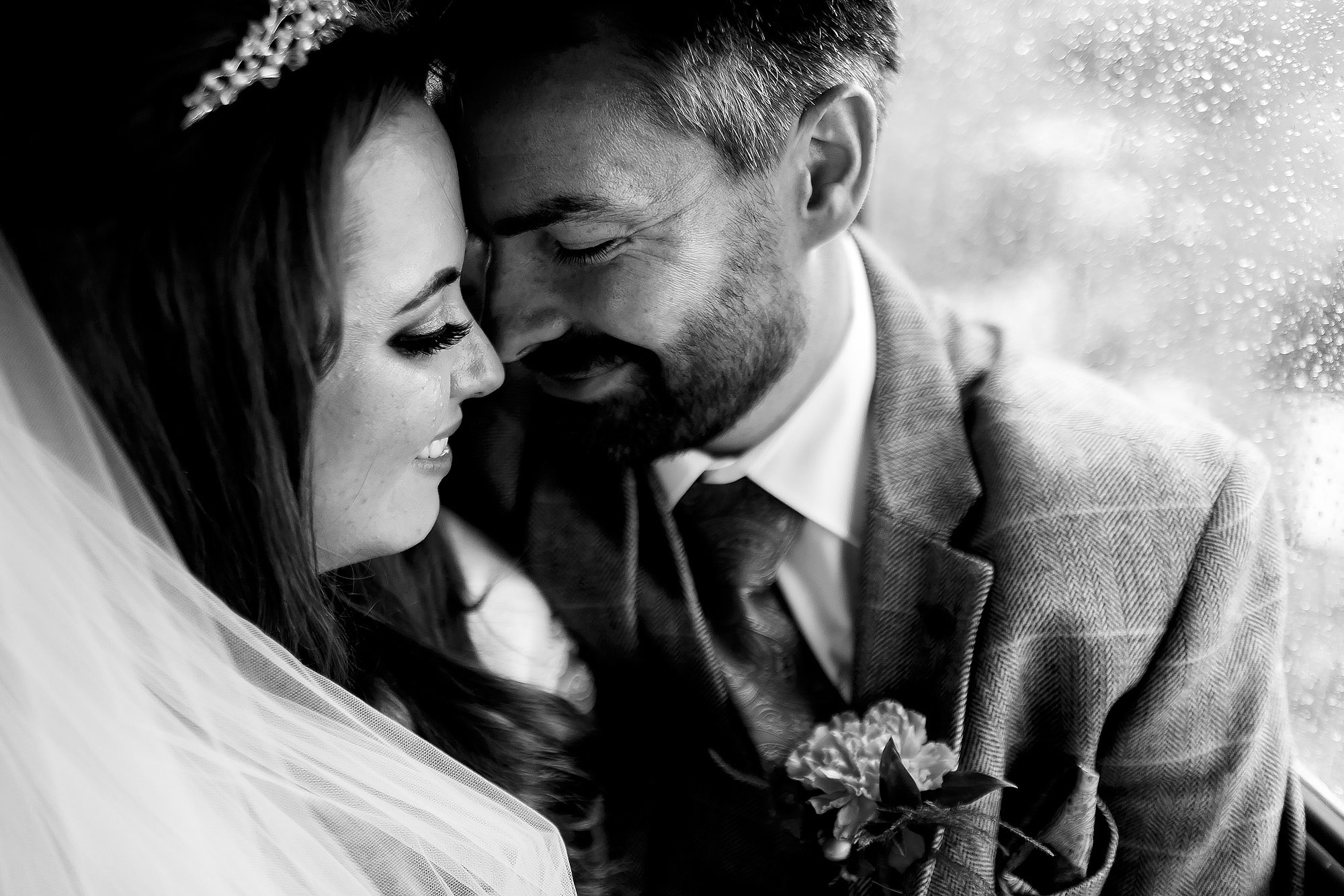 Bride and Groom enjoying a private moment on the wedding bus as rain falls on the window | Wellbeing Farm wedding photographs by Toni Darcy Photography