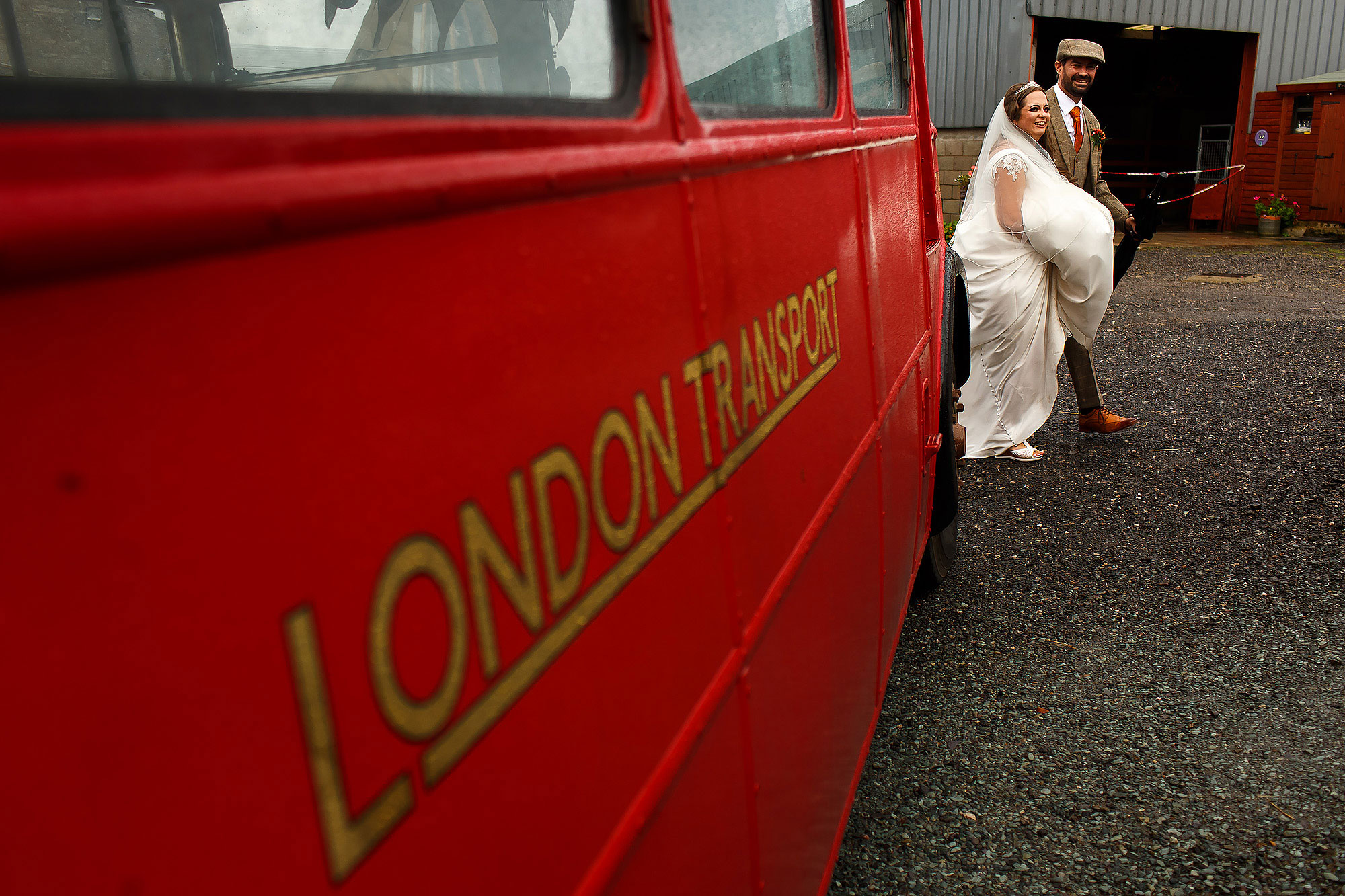 Bride and Groom walking to the wedding reception past the vintage London Transport Wedding bus | Wellbeing Farm wedding photographs by Toni Darcy Photography