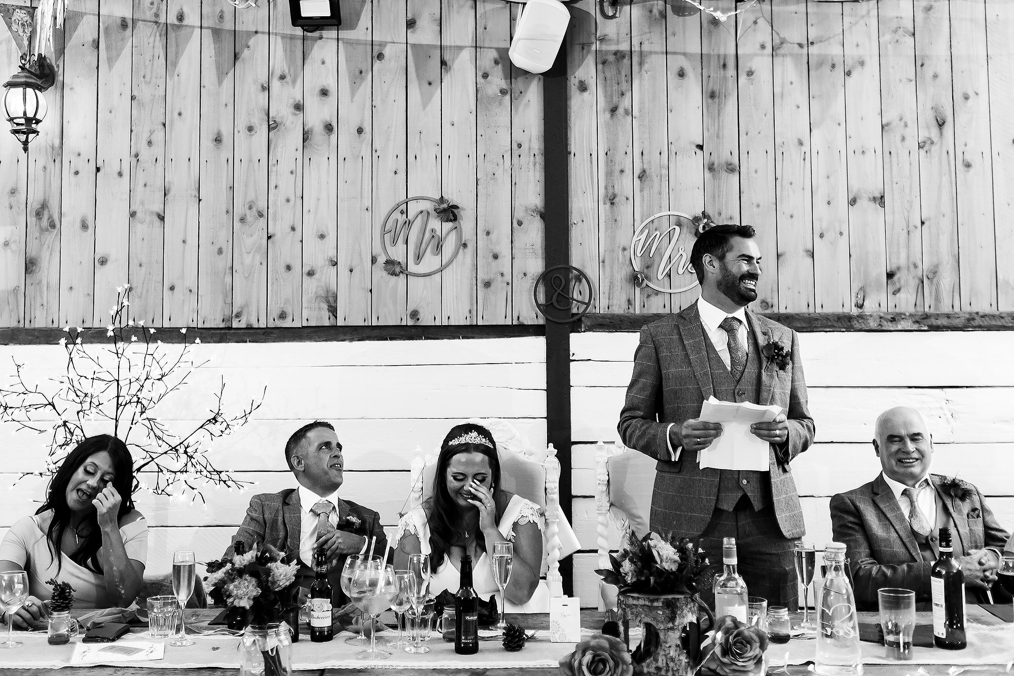 Top table of wedding guests crying laughing during speeches | Wellbeing Farm wedding photographs by Toni Darcy Photography