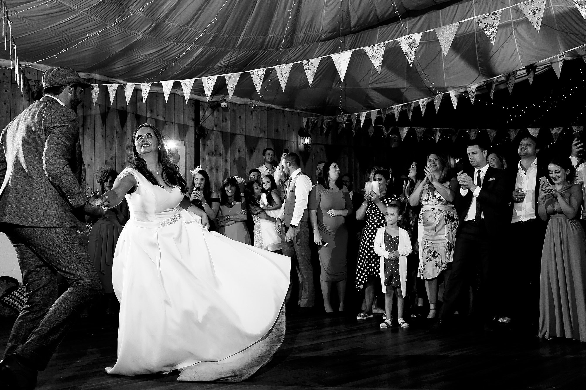 Bride twirling wedding dress as her groom spins her round the dance floor during the first dance | Wellbeing Farm wedding photographs by Toni Darcy Photography