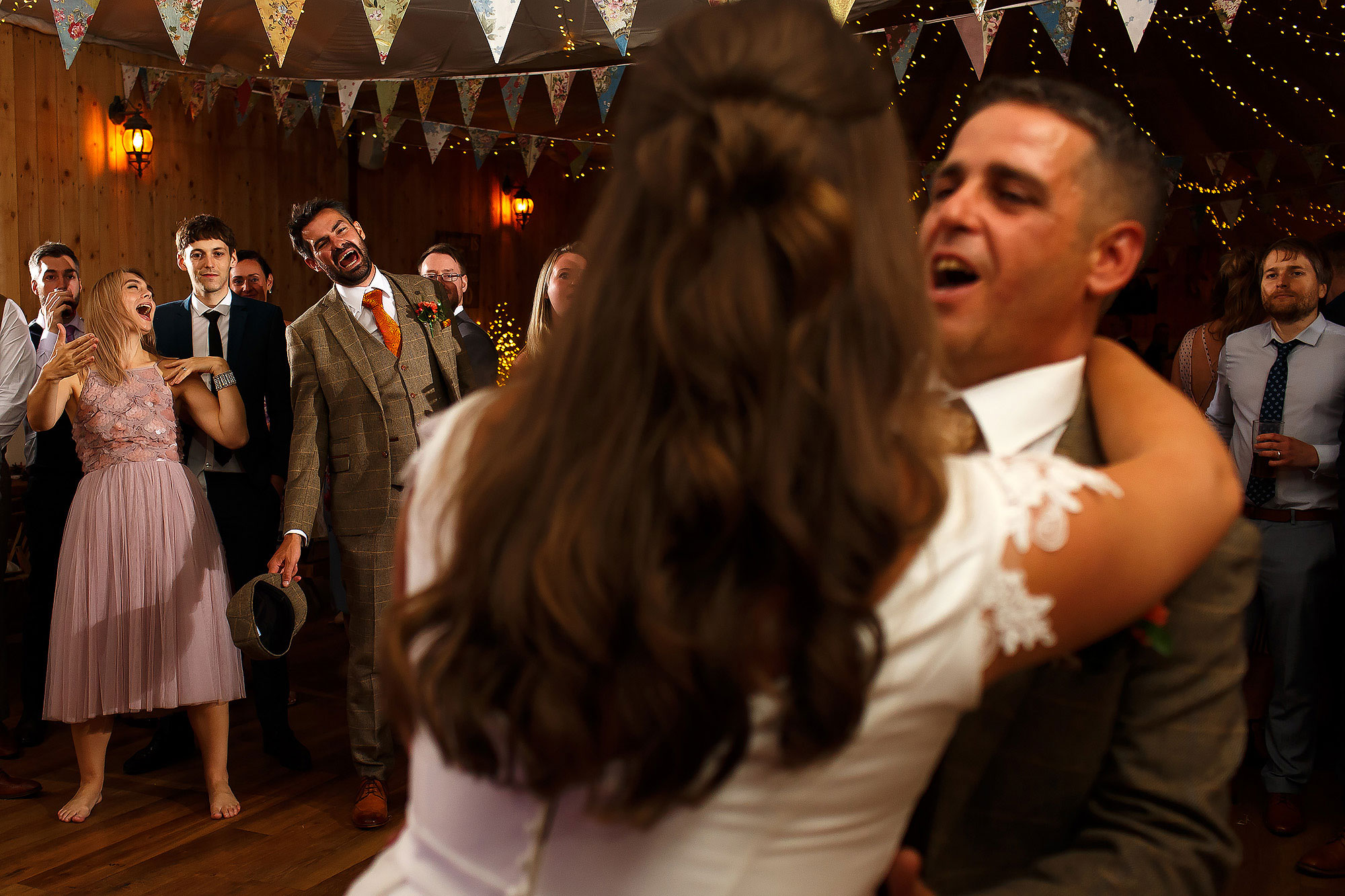 Bride dancing with her father as the wedding guests look onward singing | Wellbeing Farm wedding photographs by Toni Darcy Photography