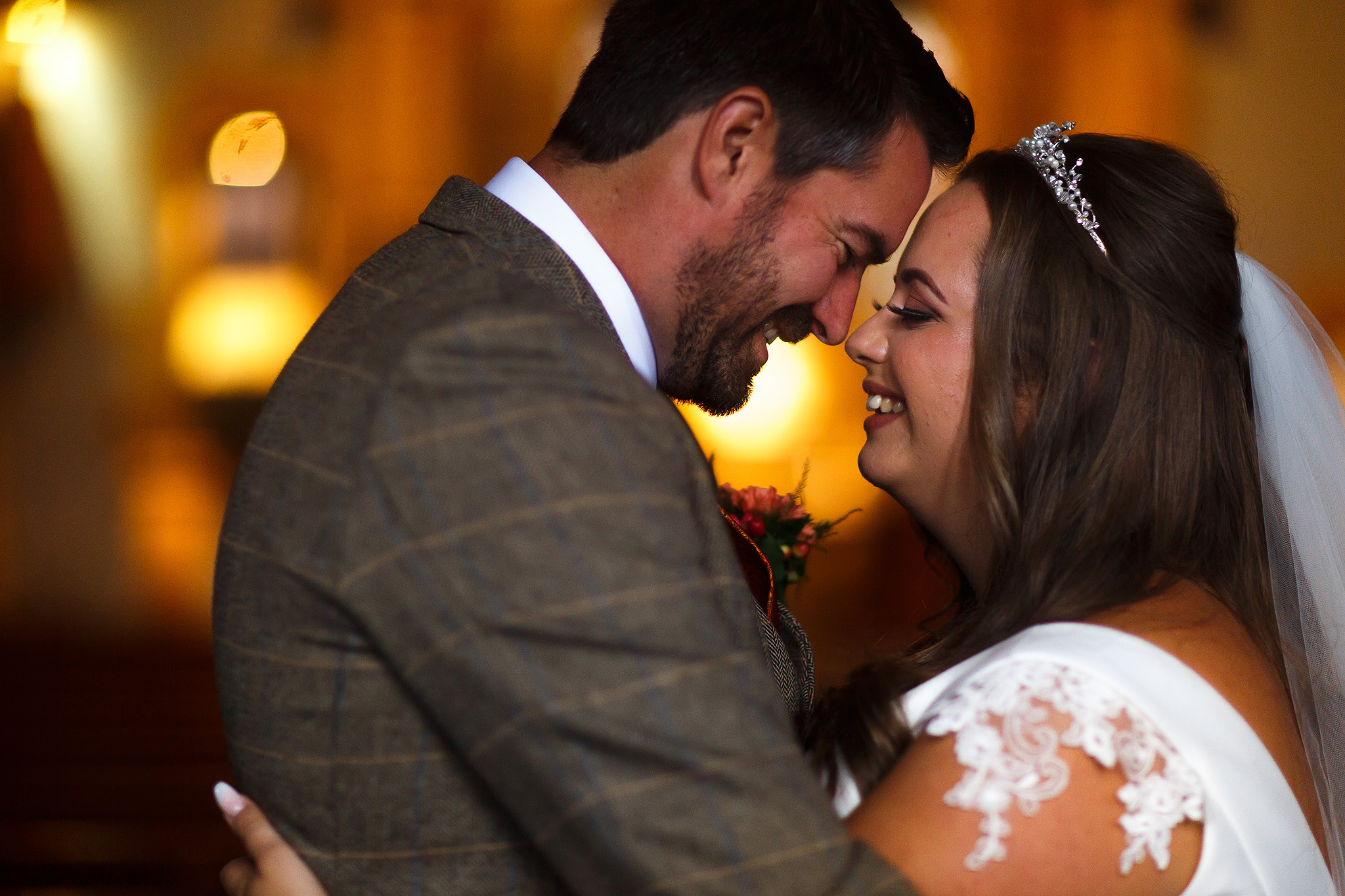 Bride with capped sleeves and long brown hair giving eskimo kisses to dark haired groom wearing tweed suit with orange lights in background.