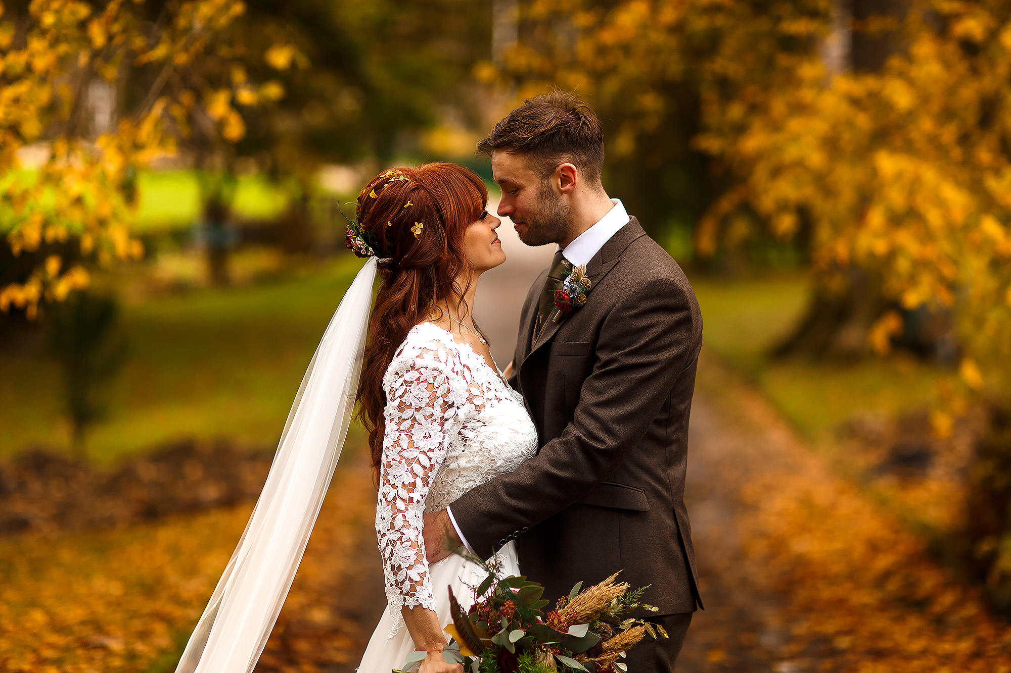 Bride and Groom stood in the tree lined drive of Browsholme Hall with Autumn leaves surrounding them - Browsholme Hall Wedding Photography