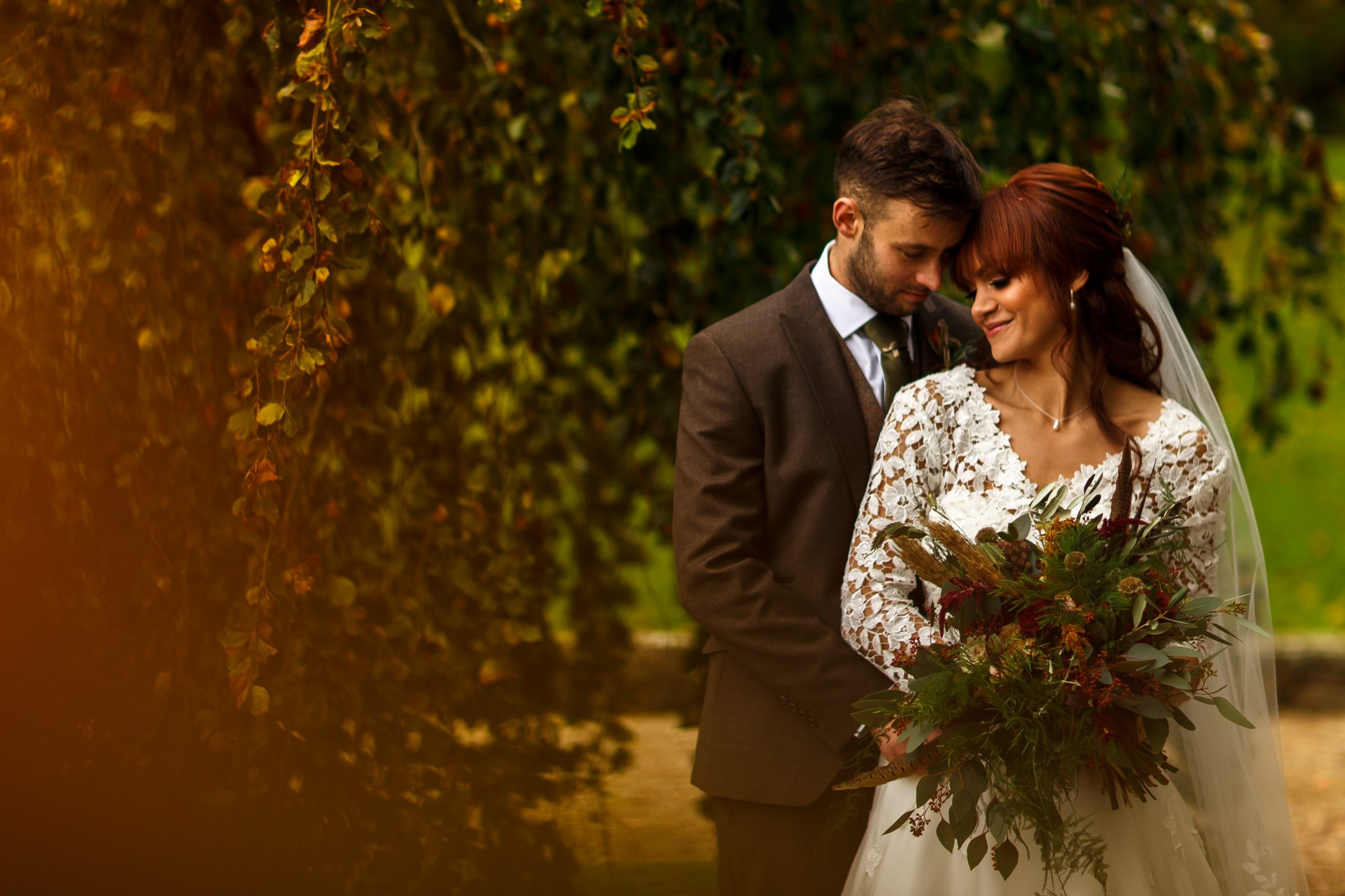 Red haired bride wearing long sleeves snuggled up to her groom