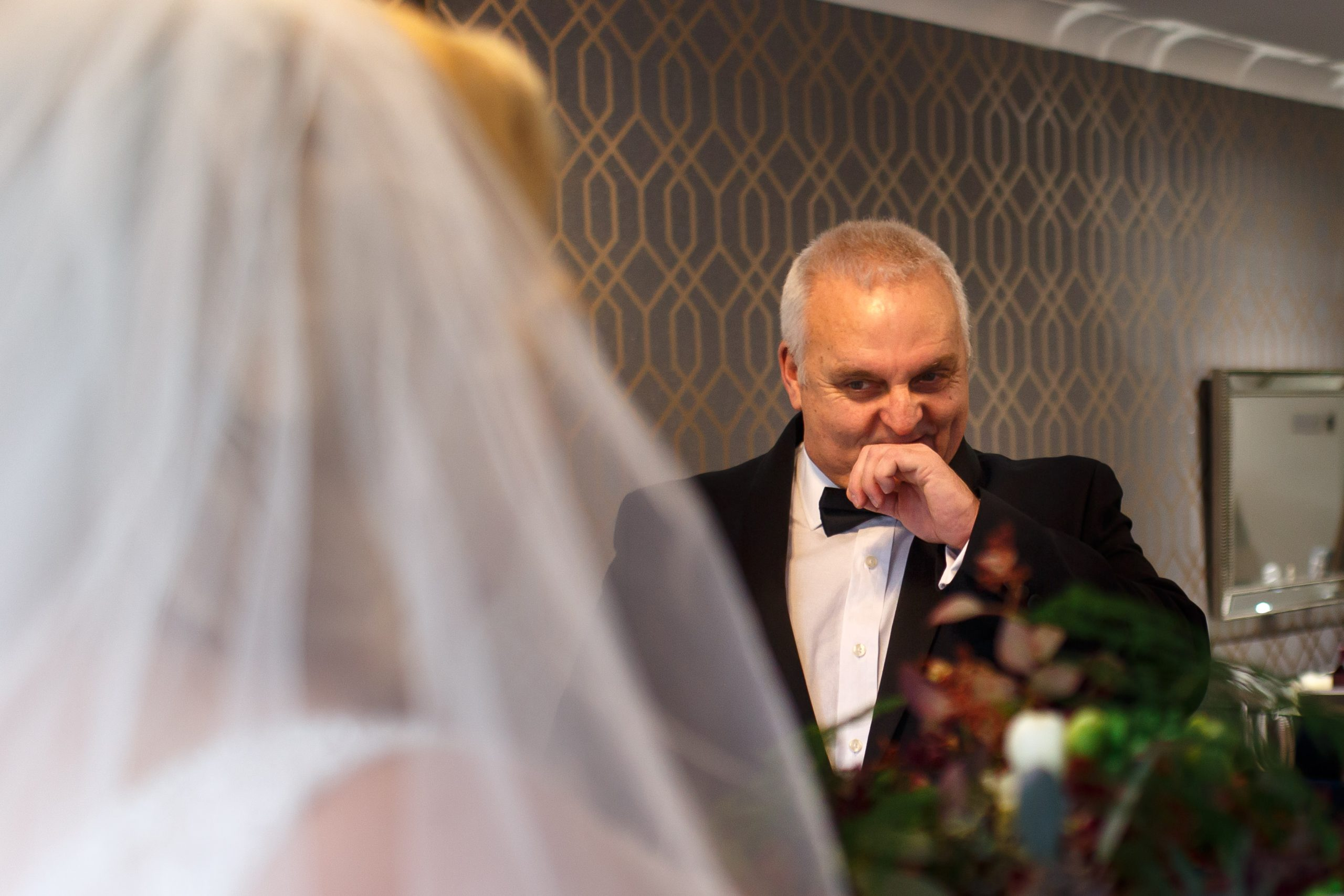 Father of the bride wearing a tuxedo holding his hand to his mouth in shock as he sees his daughter for the first time in her wedding dress | Foxfields Country House Wedding Photography