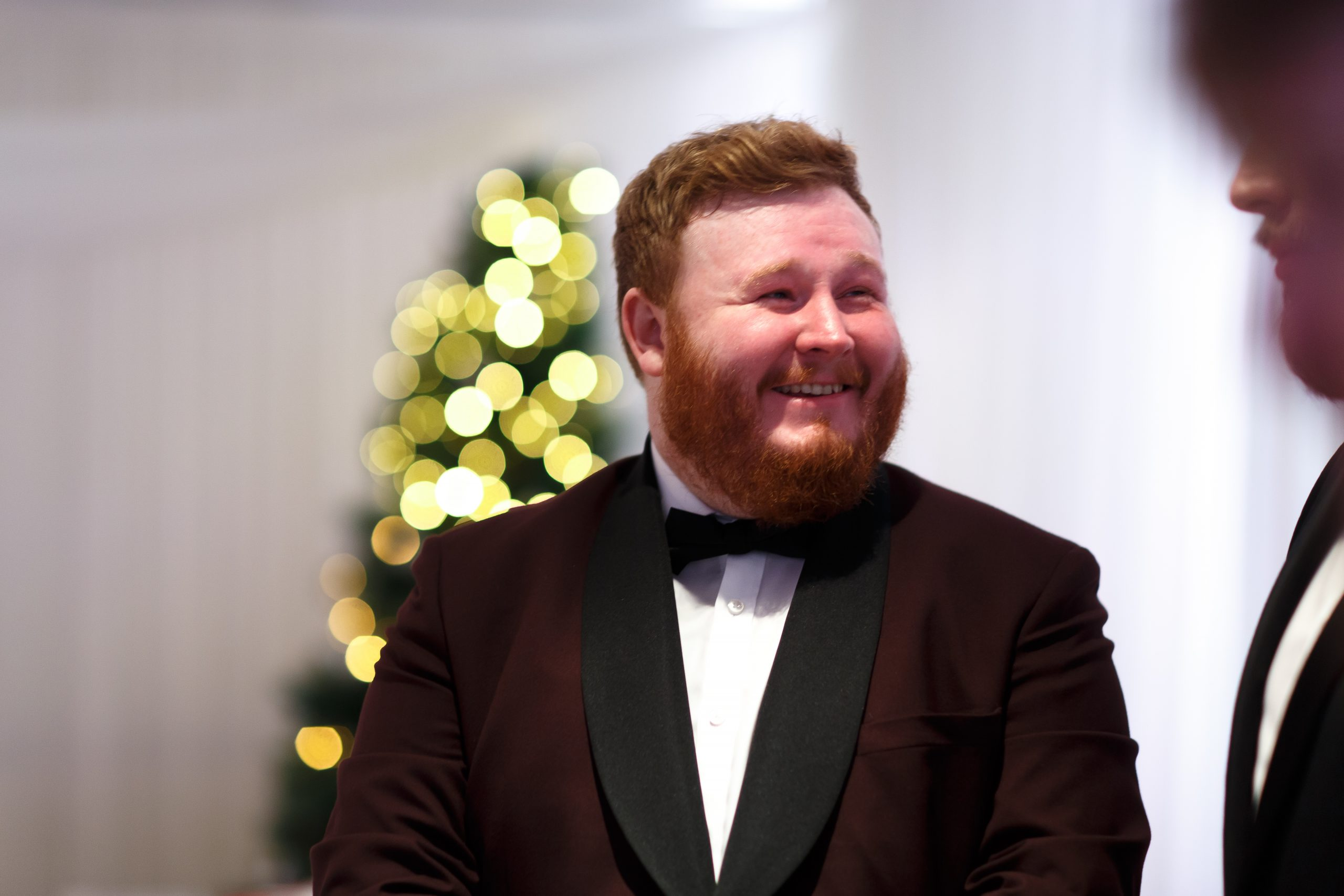 Groom with ginger hair and beard wearing maroon tuxedo | Foxfields Country House Wedding Photography