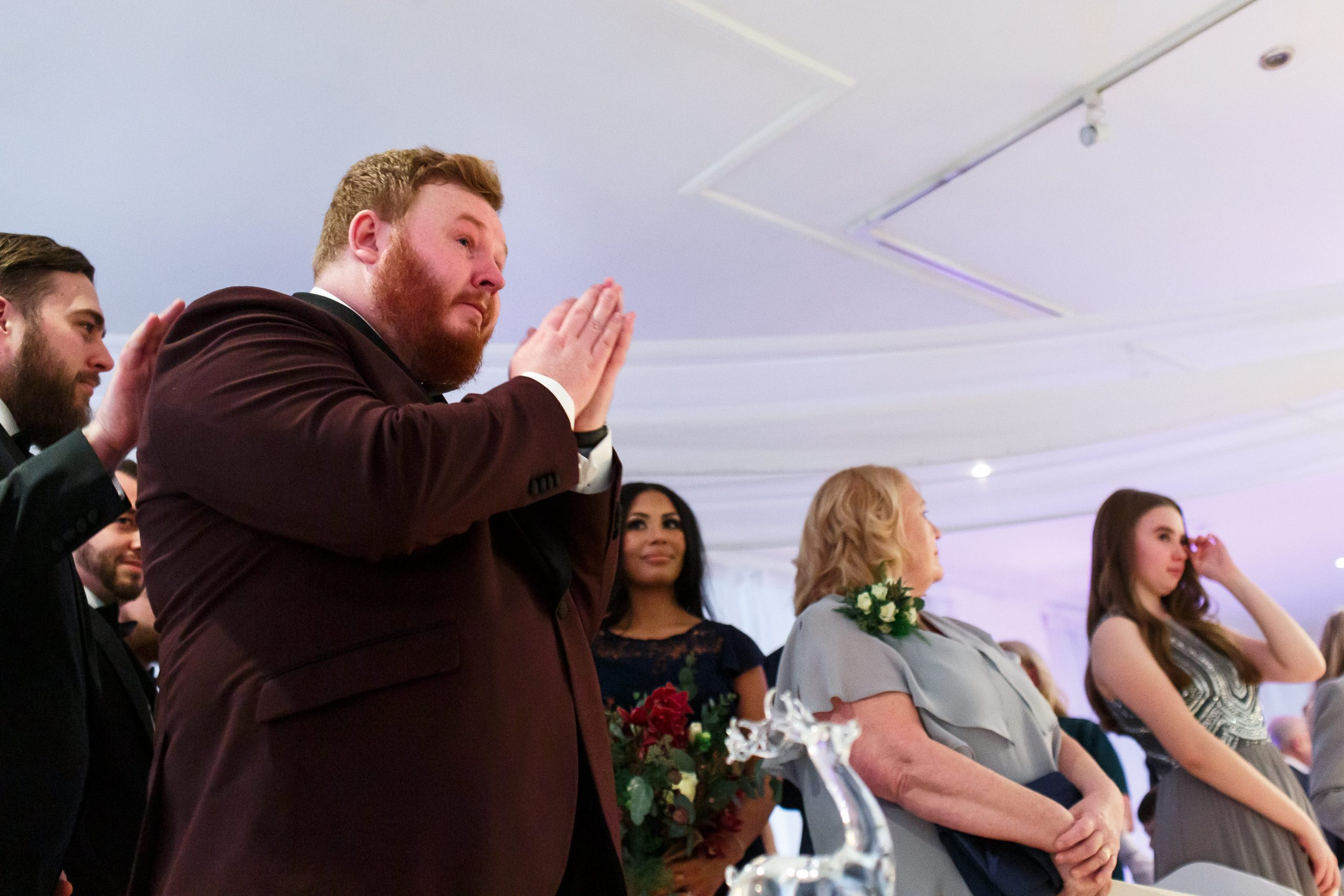 Groom with ginger hair and maroon tuxedo holding his hands to pray as his bride walks down the aisle | Foxfields Country House Wedding Photography