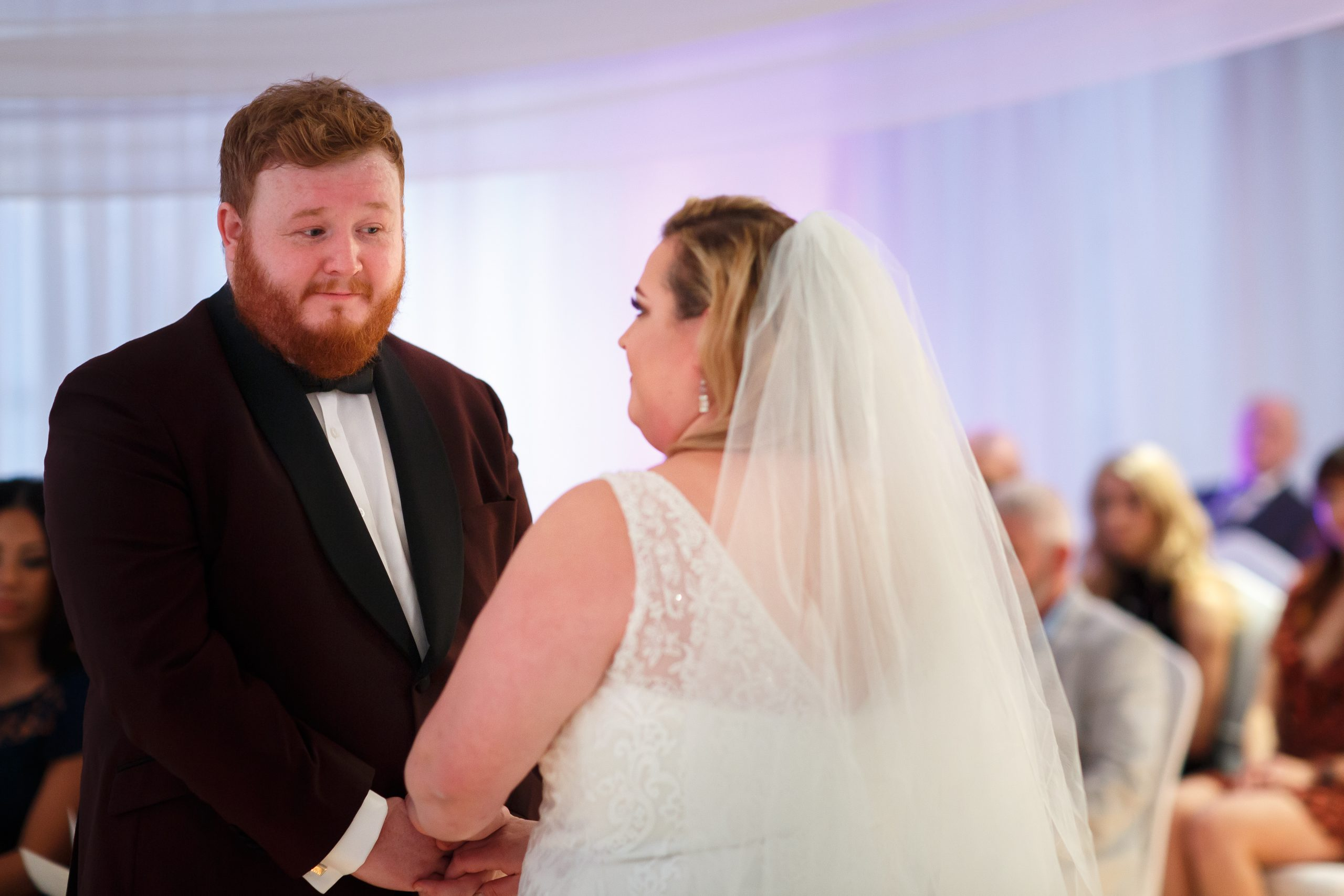 Groom with ginger and beard hair looking emotionally towards bride during wedding ceremony | Foxfields Country House Wedding Photography