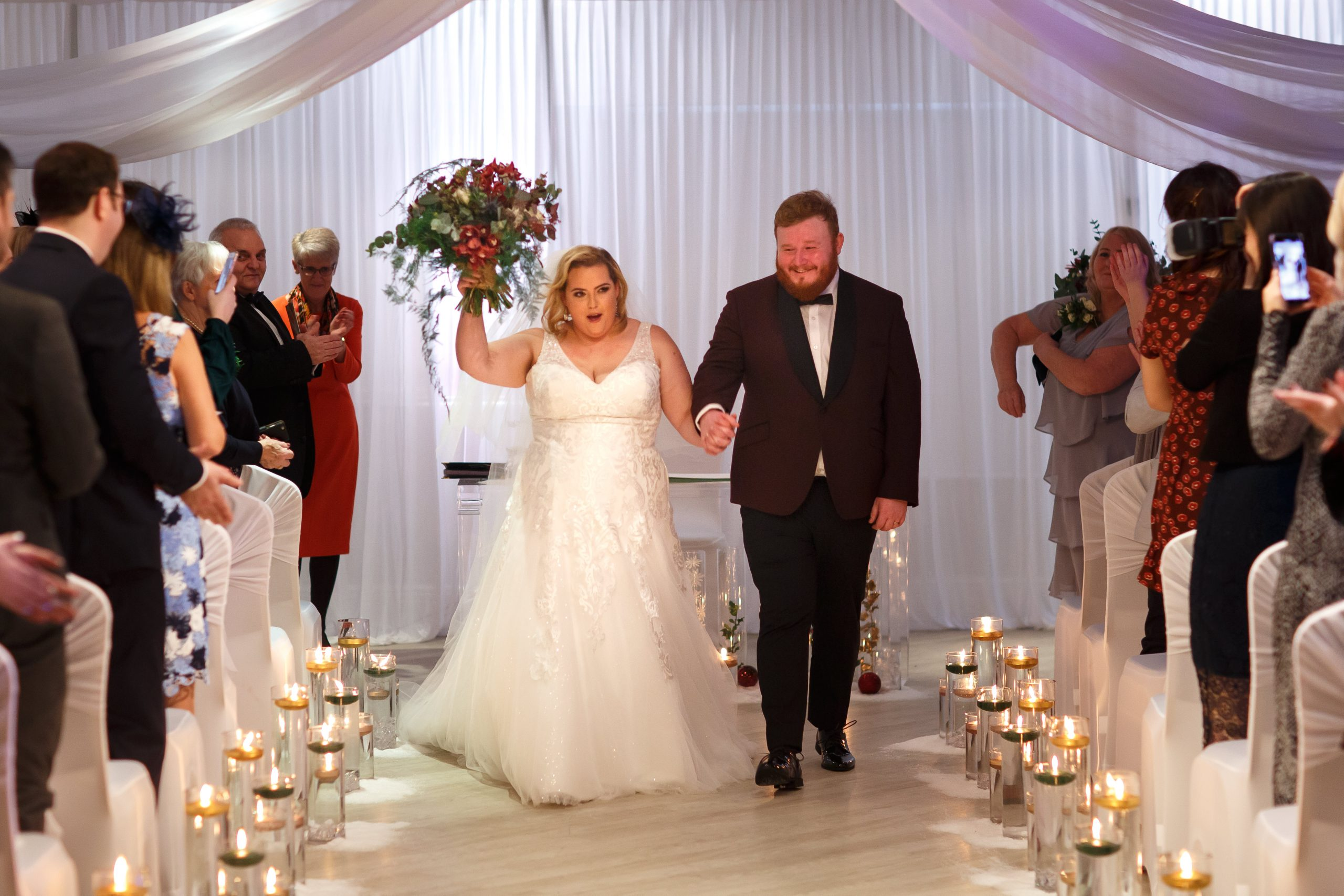 Bride waving wedding flowers in the air as she walks down the candle lit aisle with her new husband | Foxfields Country House Wedding Photography