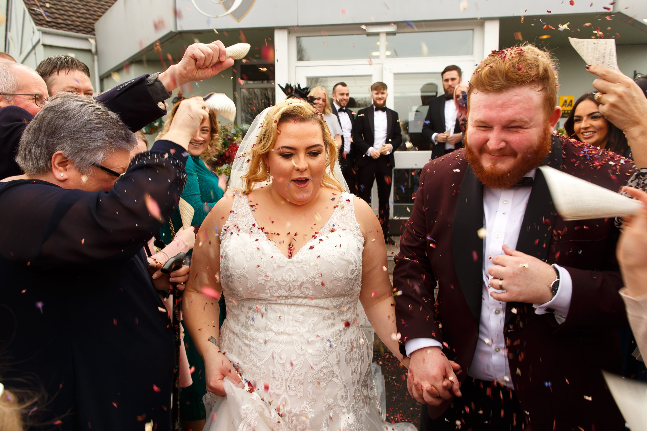 Bride and groom being showered in colourful confetti | Foxfields Country House Wedding Photography