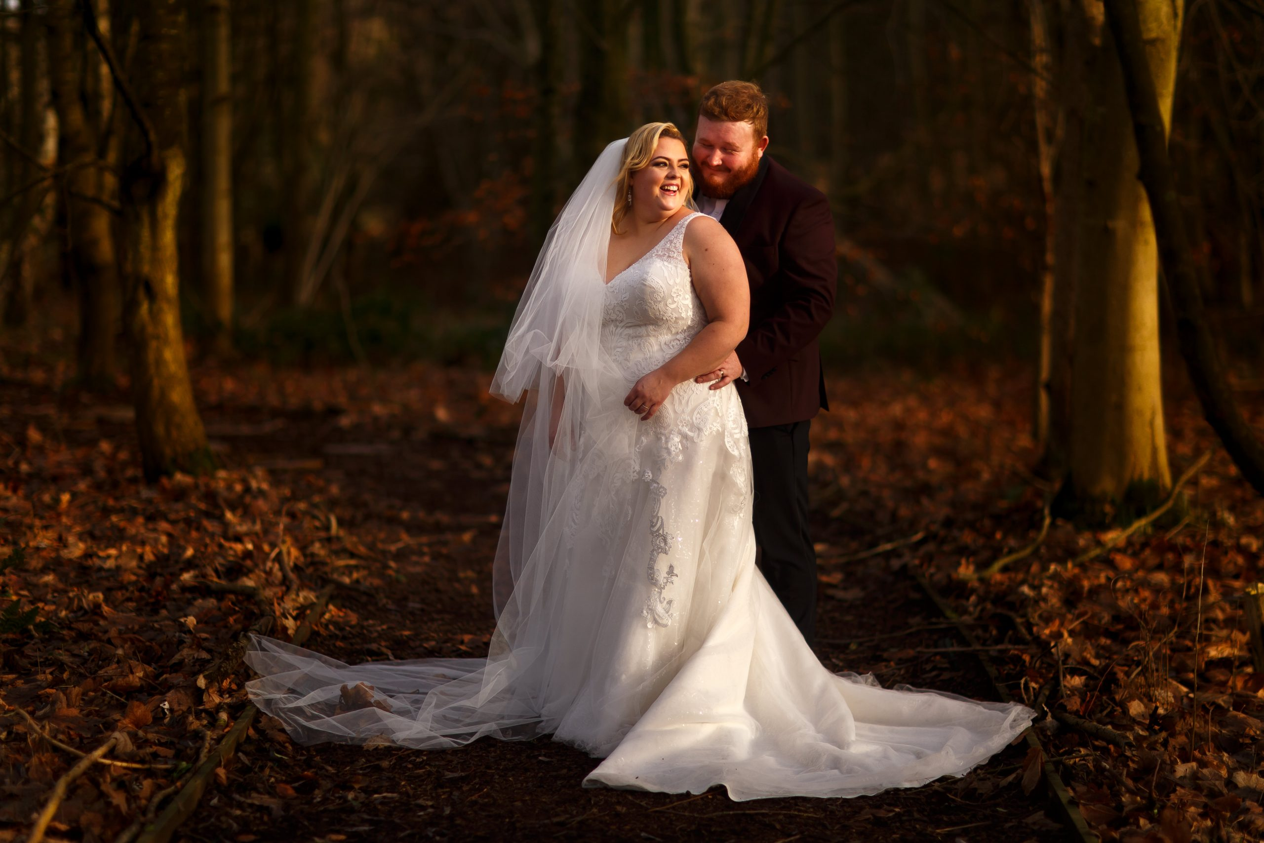 Bride with blonde hair and long veil laughing towards her ginger haired groom in the woodland at Foxfields Whalley | Foxfields Country House Wedding Photography