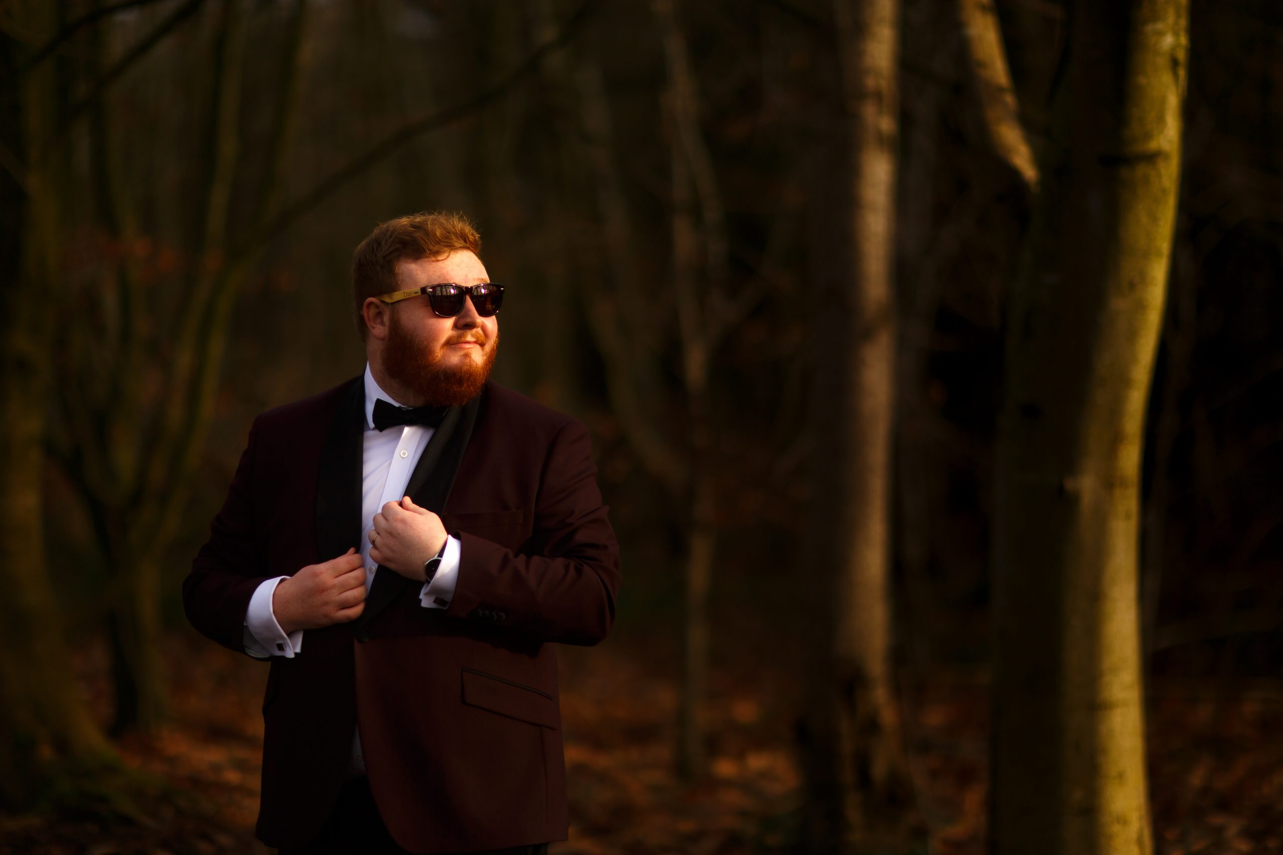 Groom wearing maroon tuxedo in the woodland at Foxfields Country house wearing sunglasses | Foxfields Country House Wedding Photography