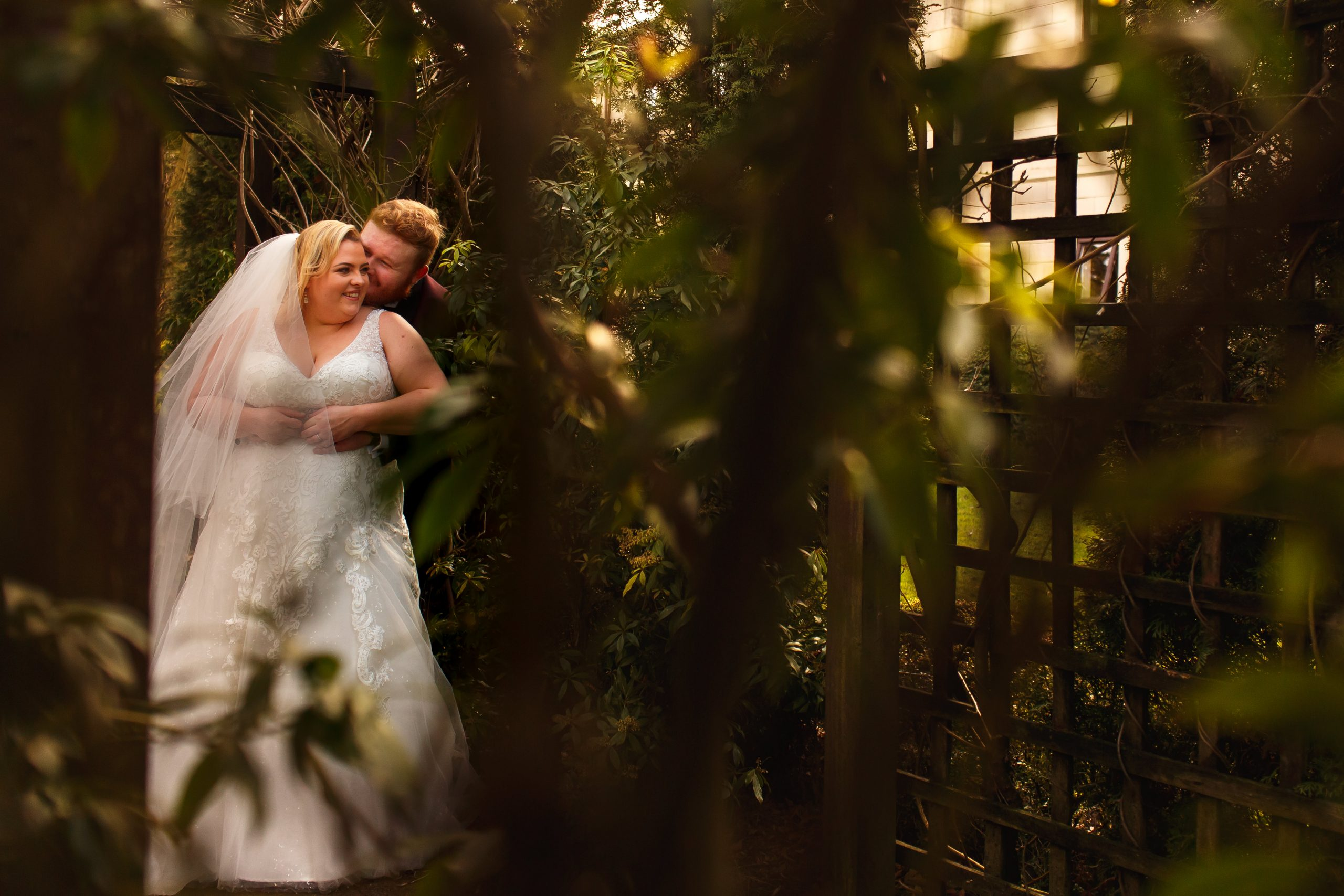 Groom bear hugging bride from behind kissing her cheek surrounded by plants in the gardens at Foxfields Whalley | Foxfields Country House Wedding Photography