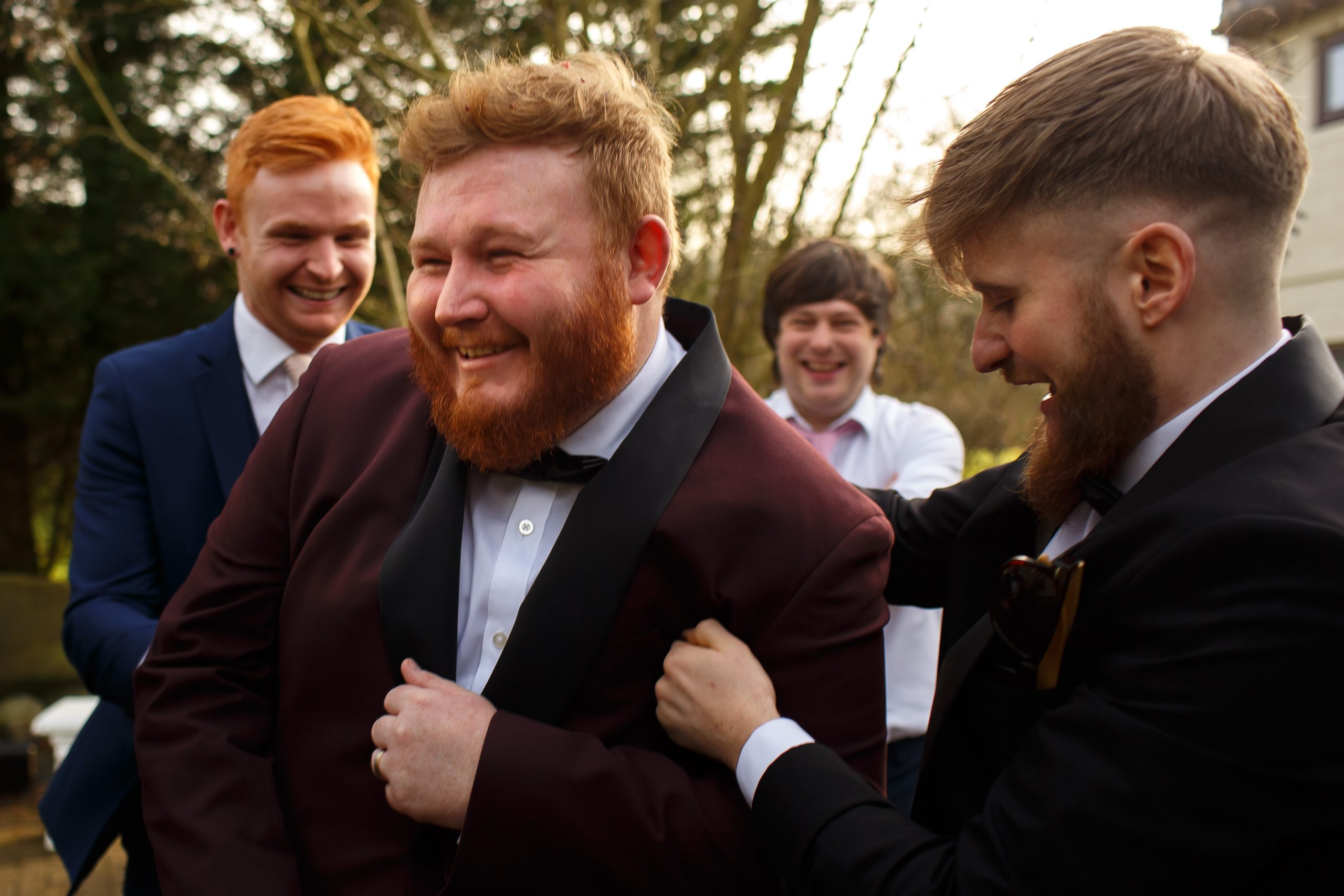 Groom with ginger hair wearing maroon tuxedo being hugged by his smiling friends | Foxfields Country House Wedding Photography