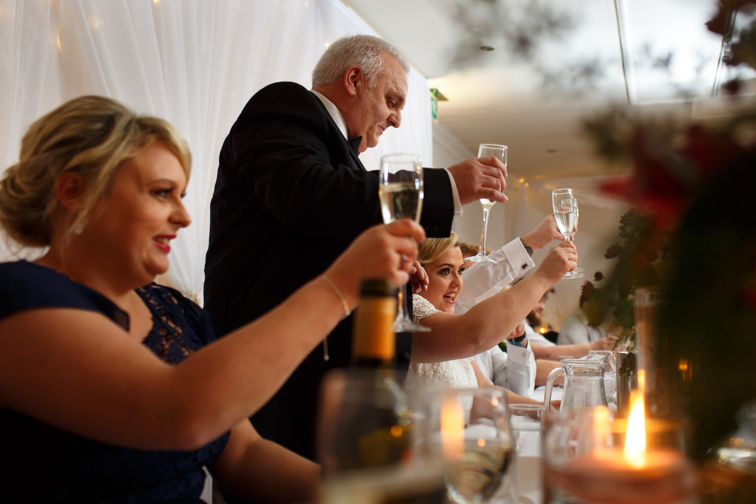 Top table raising glasses to cheers during wedding speeches | Foxfields Country House Wedding Photography