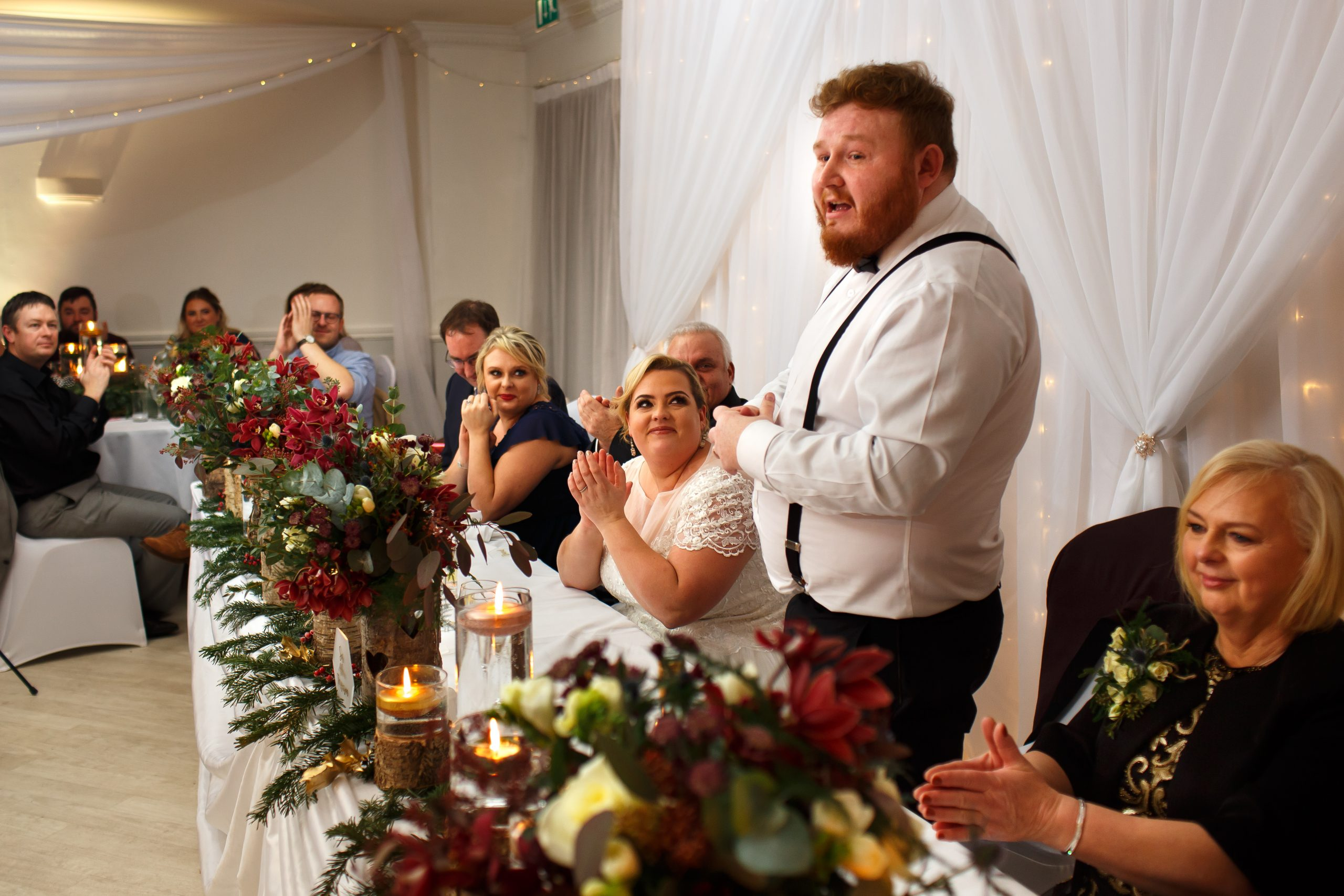 Groom standing behind the top table wearing braces during wedding speeches | Foxfields Country House Wedding Photography