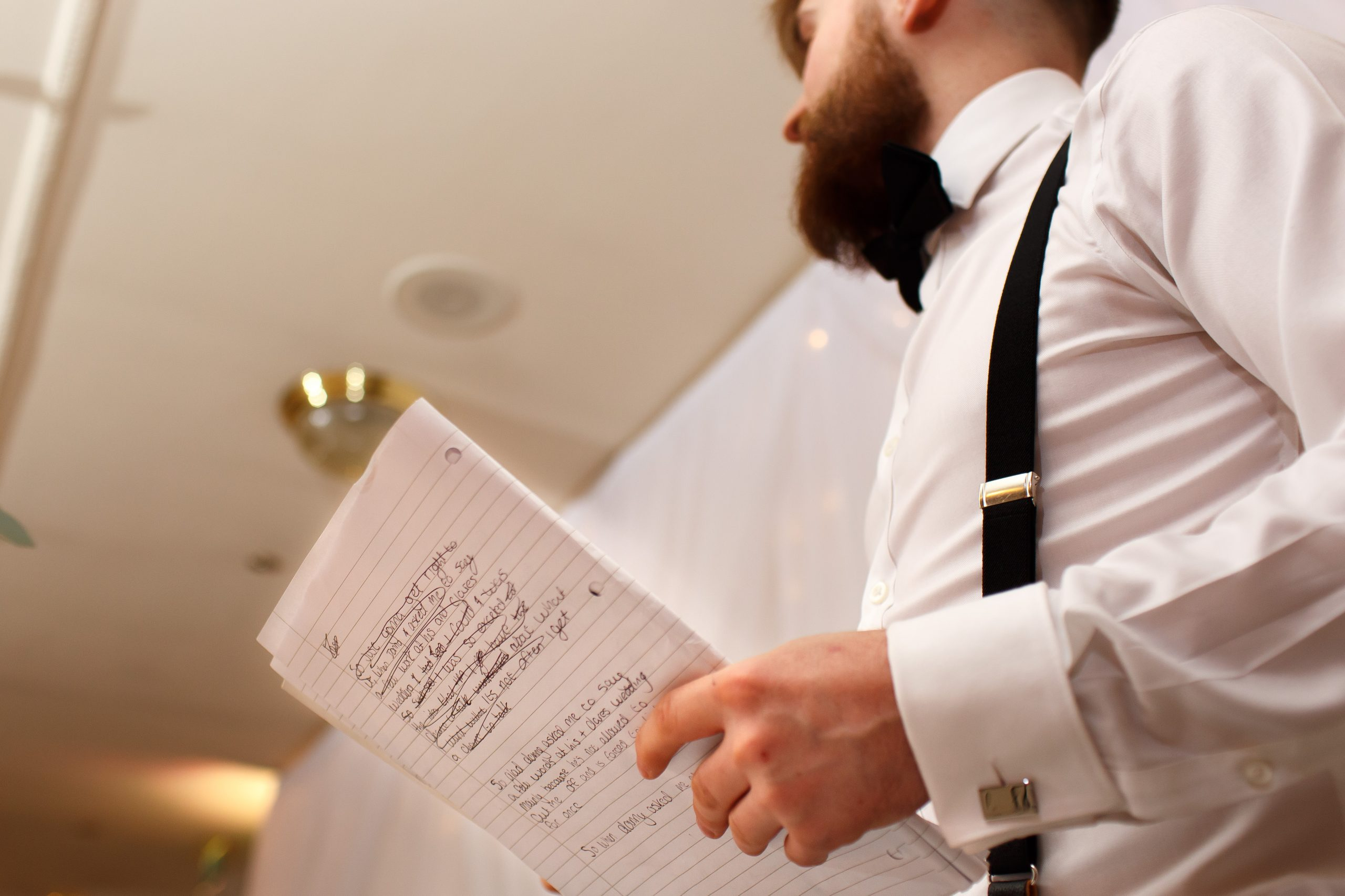 Best man wearing braces holding his hand written speech as he reads | Foxfields Country House Wedding Photography