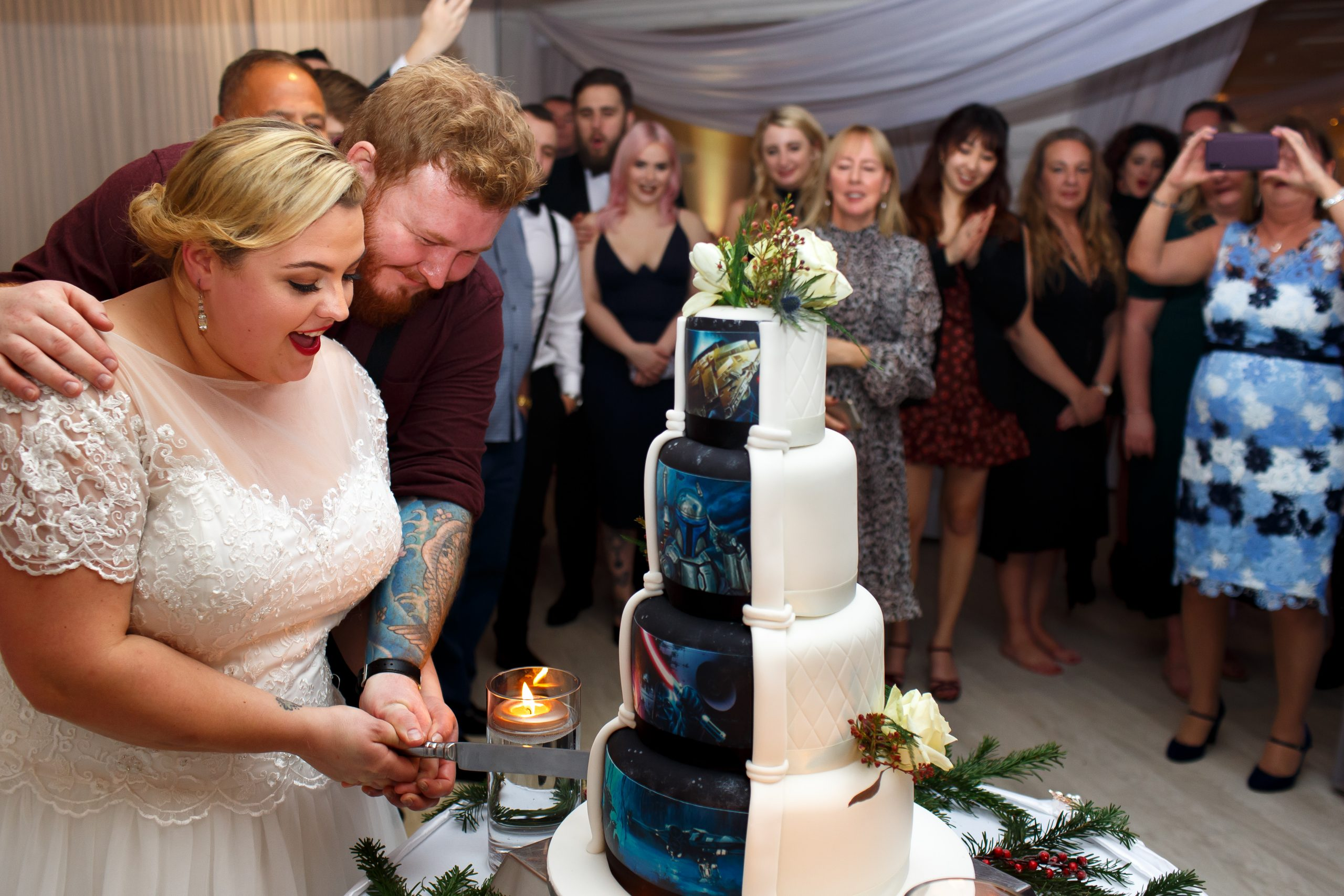 Bride and groom cutting the hidden back of wedding cake with star wars design hiding behind the plain front tiers | Foxfields Country House Wedding Photography