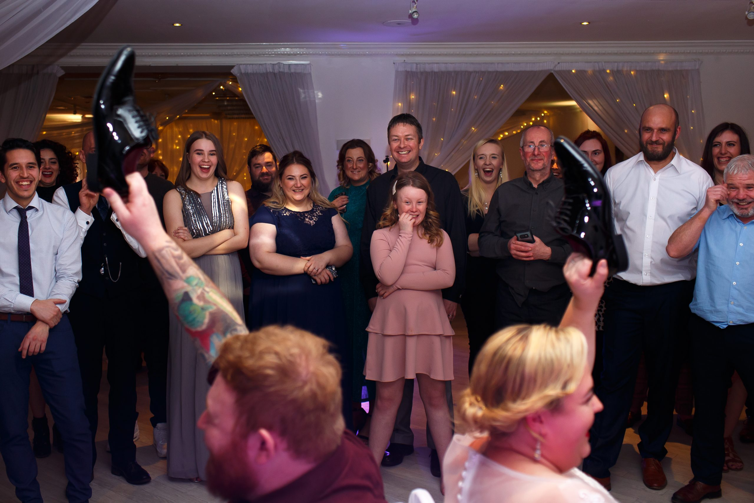 Wedding guests laughing as the bride and groom play mr and mrs during wedding reception | Foxfields Country House Wedding Photography