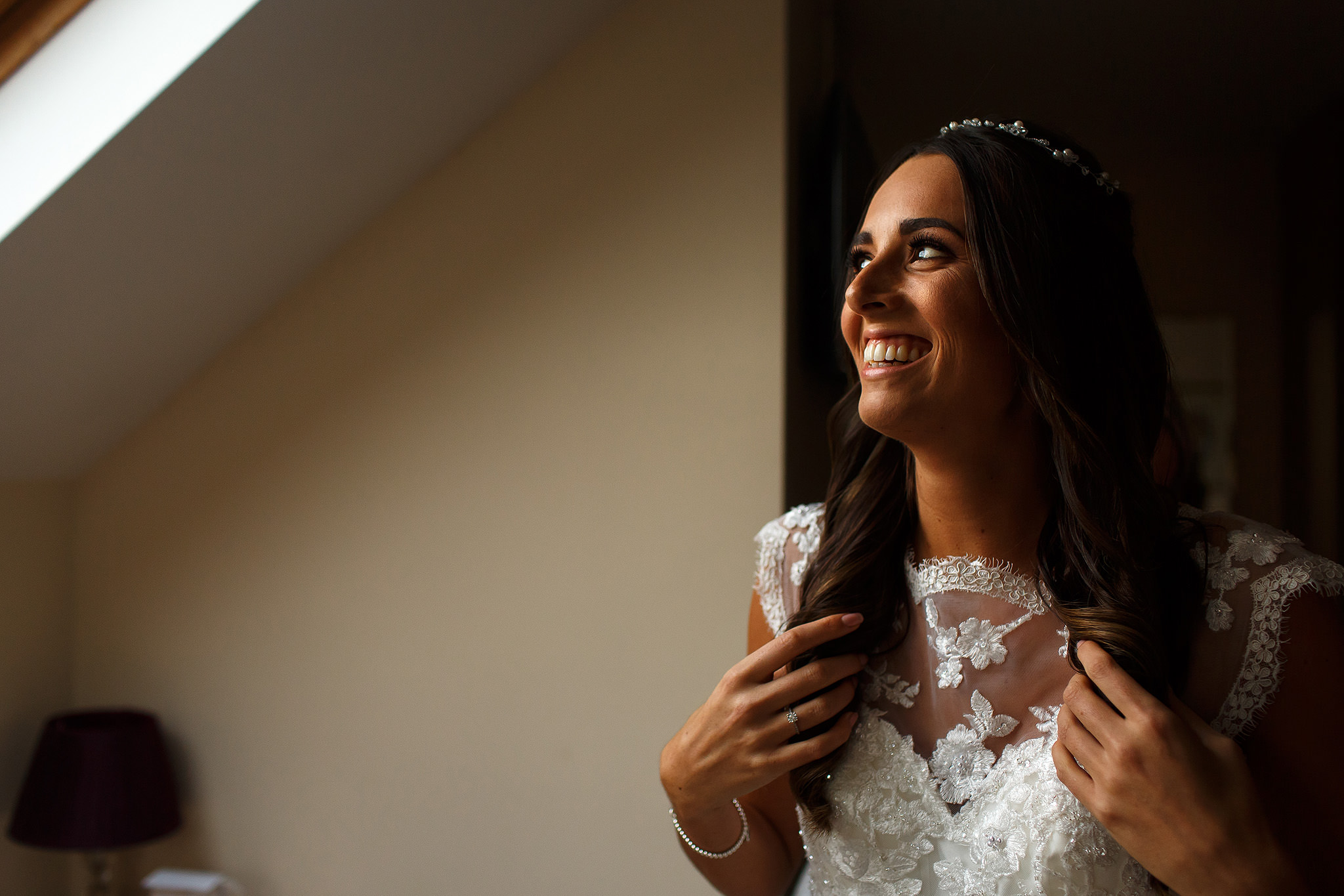 bride with long brunette hair wearing lace wedding dress smiling out the window