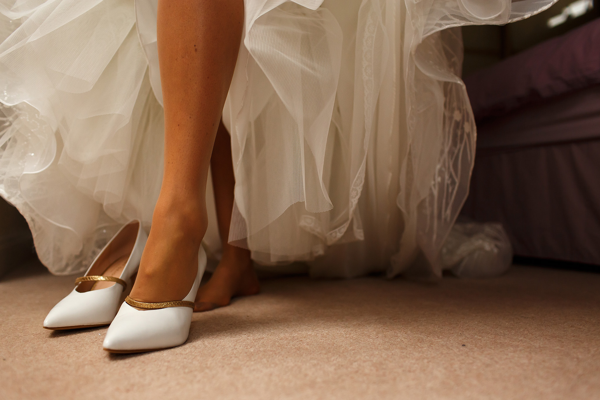 Bride with long legs stepping into her white wedding shoes with wedding dress falling behind