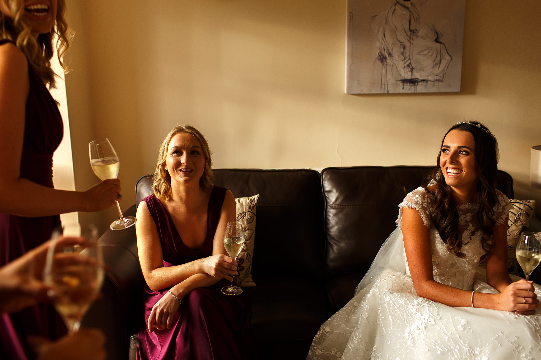 Bride wearing long lace dress sat down drinking champagne as she laughs with bridesmaids wearing long berry wine coloured dresses