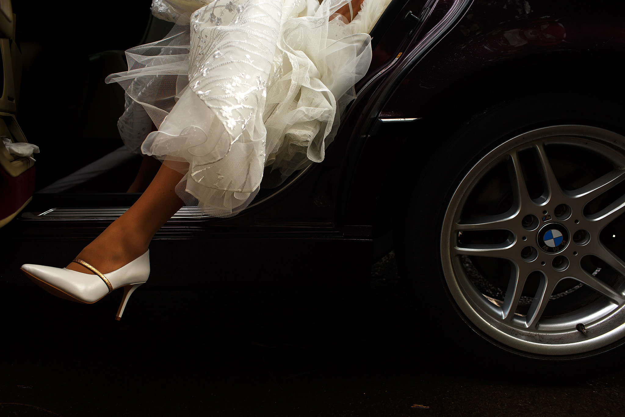 Bride stepping out of black wedding car with just the leg and shoe showing in the image | Nunsmere Hall Wedding Photography