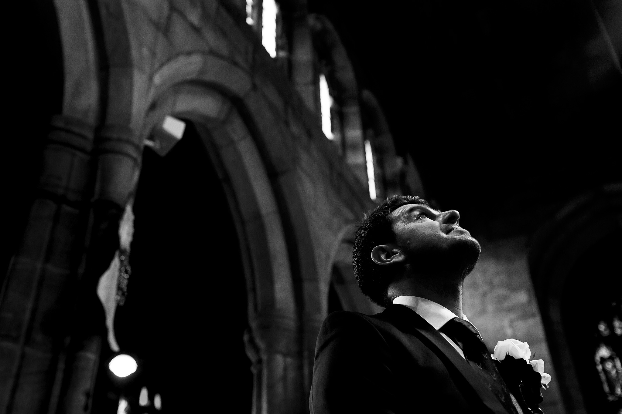 Black and white image of groom looking up feeling emotional as he waits inside the church