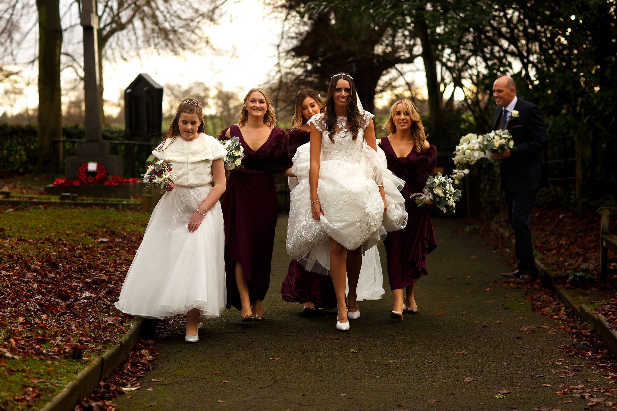 Bride holding long wedding dress up as she walks down the church pathway