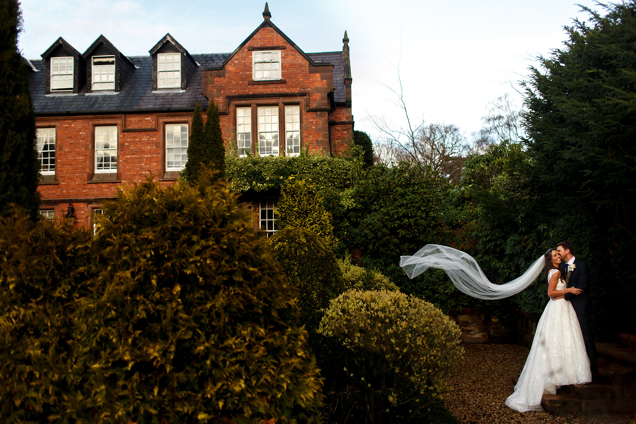 Bride wearing long lace wedding dress with sequin underskirt holding onto groom in the gardens of Nunsmere Hall as her long wedding veil flows behind them showing the Hall in the background