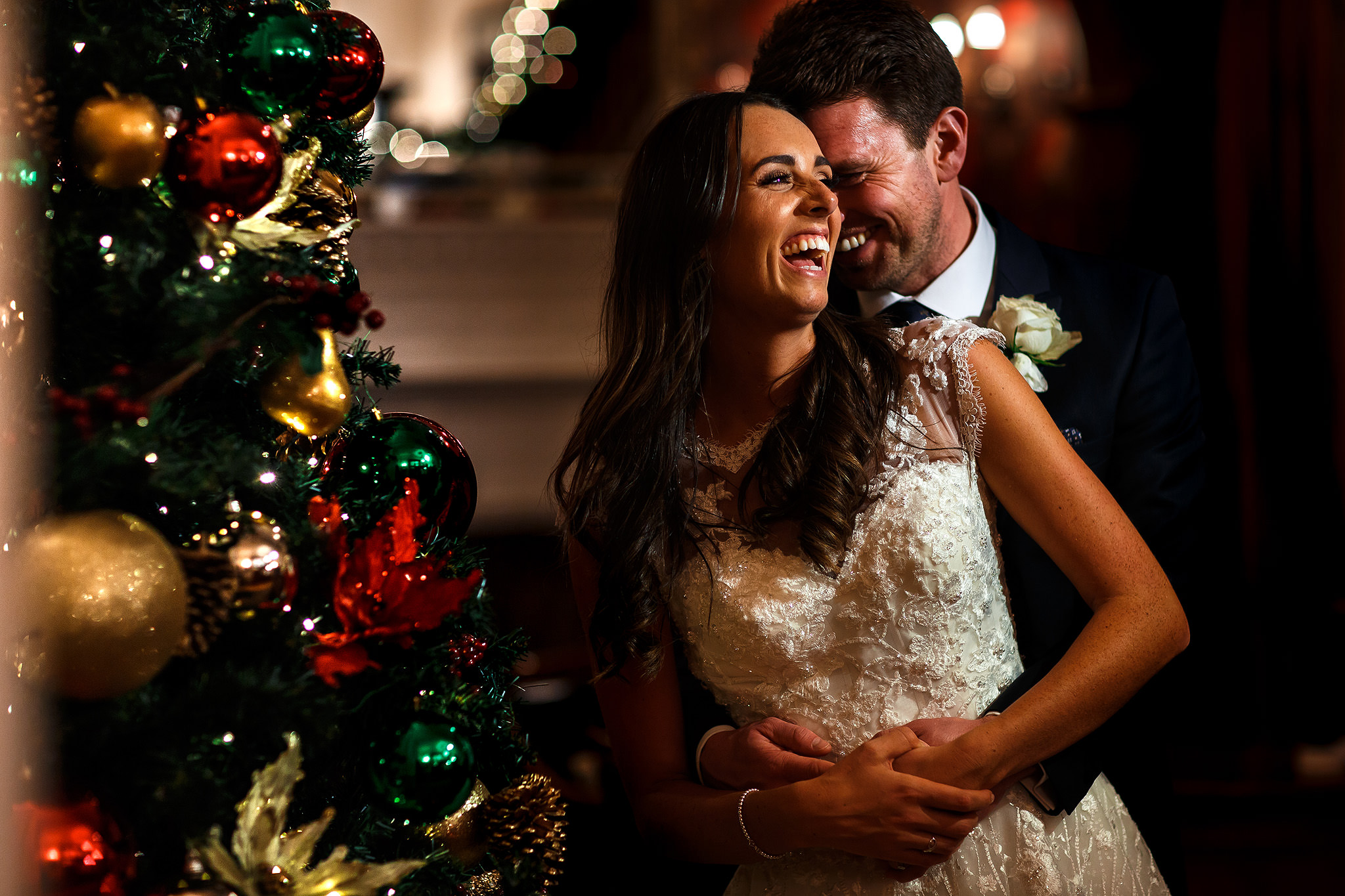 Bride and groom laughing in front of a Christmas Tree at Nunsmere Hall wedding