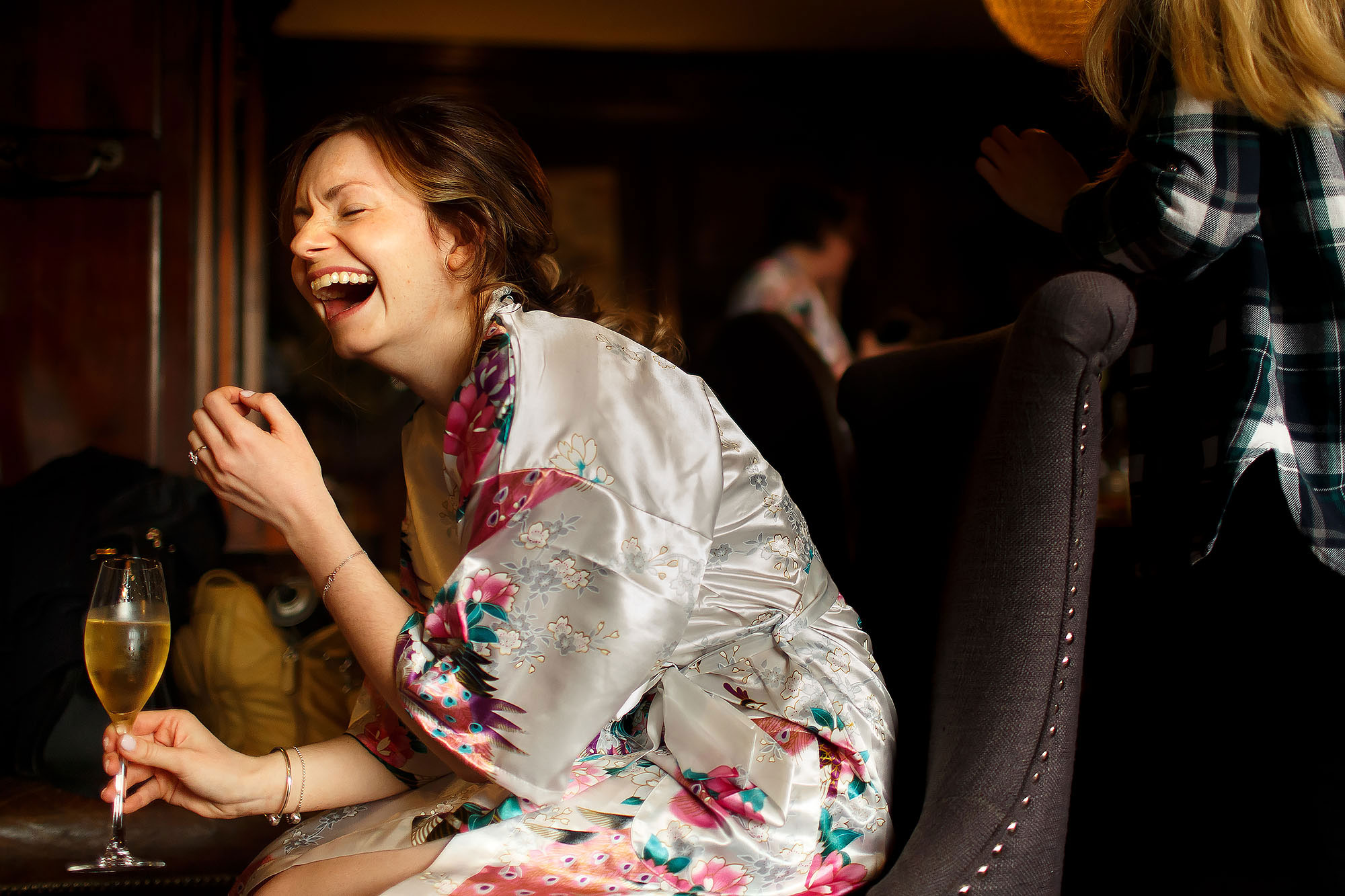 Bride laughing uncontrollably whilst sipping champagne in dressing gown | Mitton Hall wedding photographs by Toni Darcy Photography