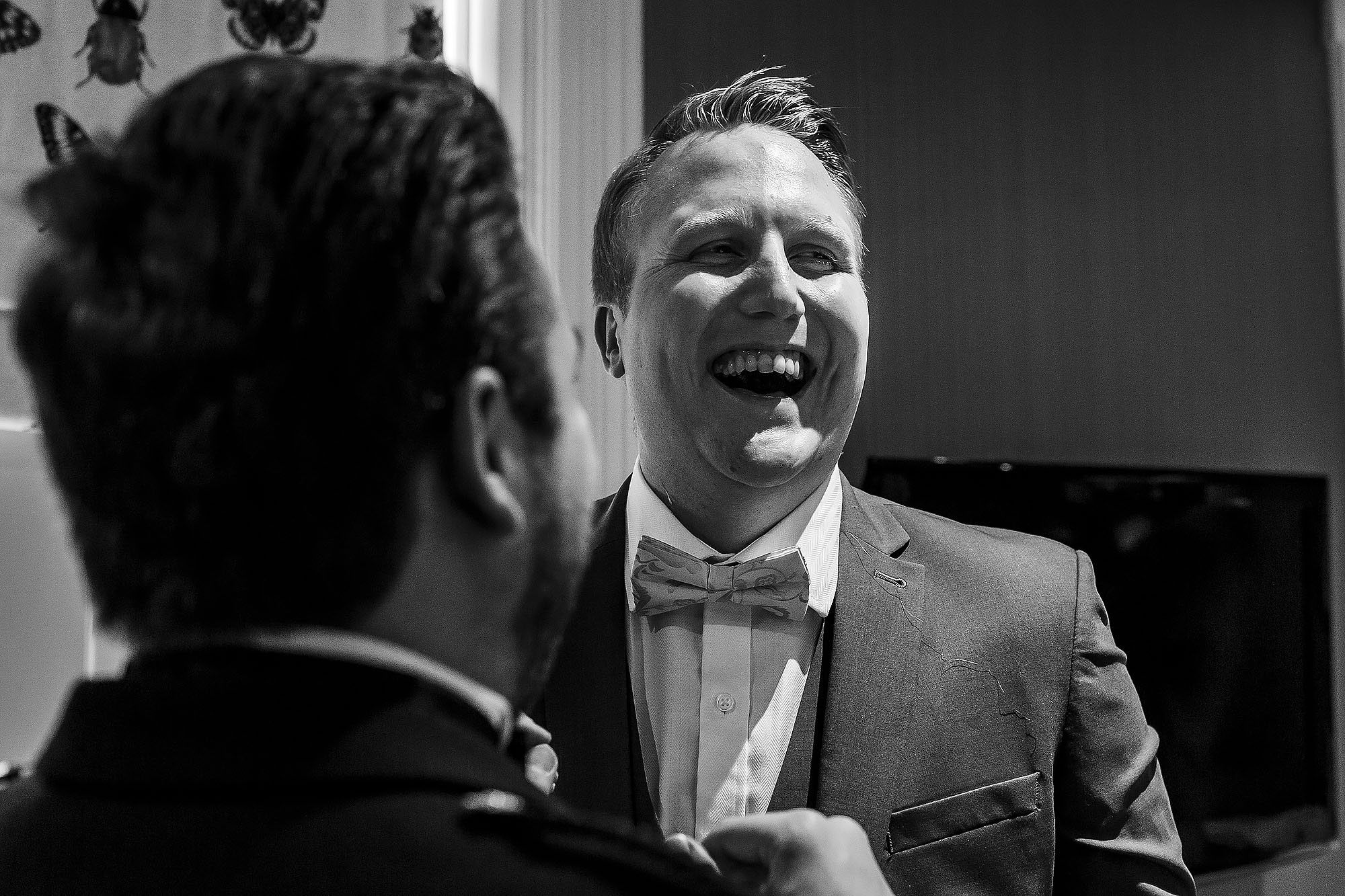 Groom wearing bow tie laughing as his suit is adjusted | Mitton Hall wedding photographs by Toni Darcy Photography