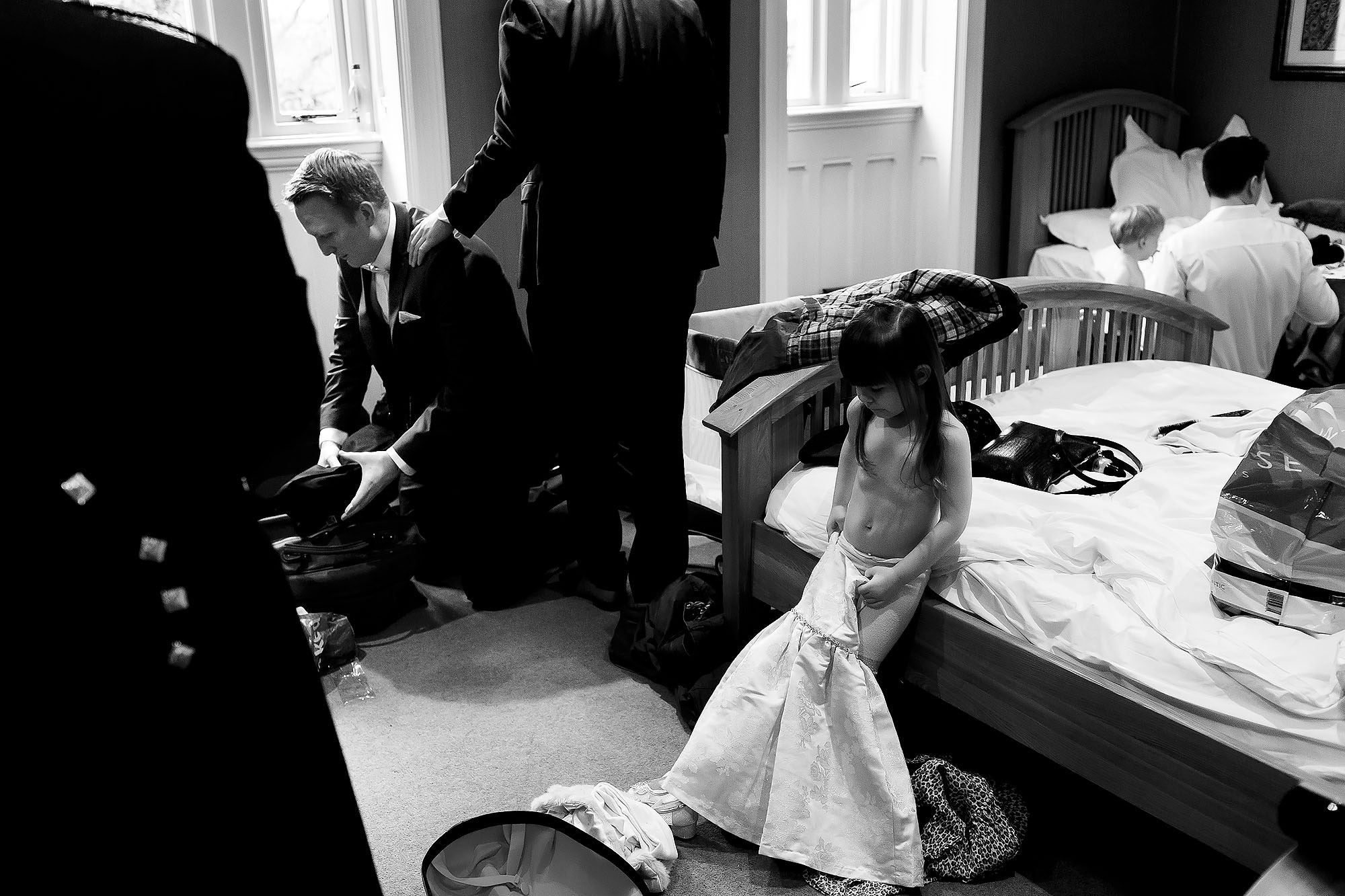 Documentary wedding scene of groomsmen getting ready while flower girls tries to dress herself | Mitton Hall wedding photographs by Toni Darcy Photography