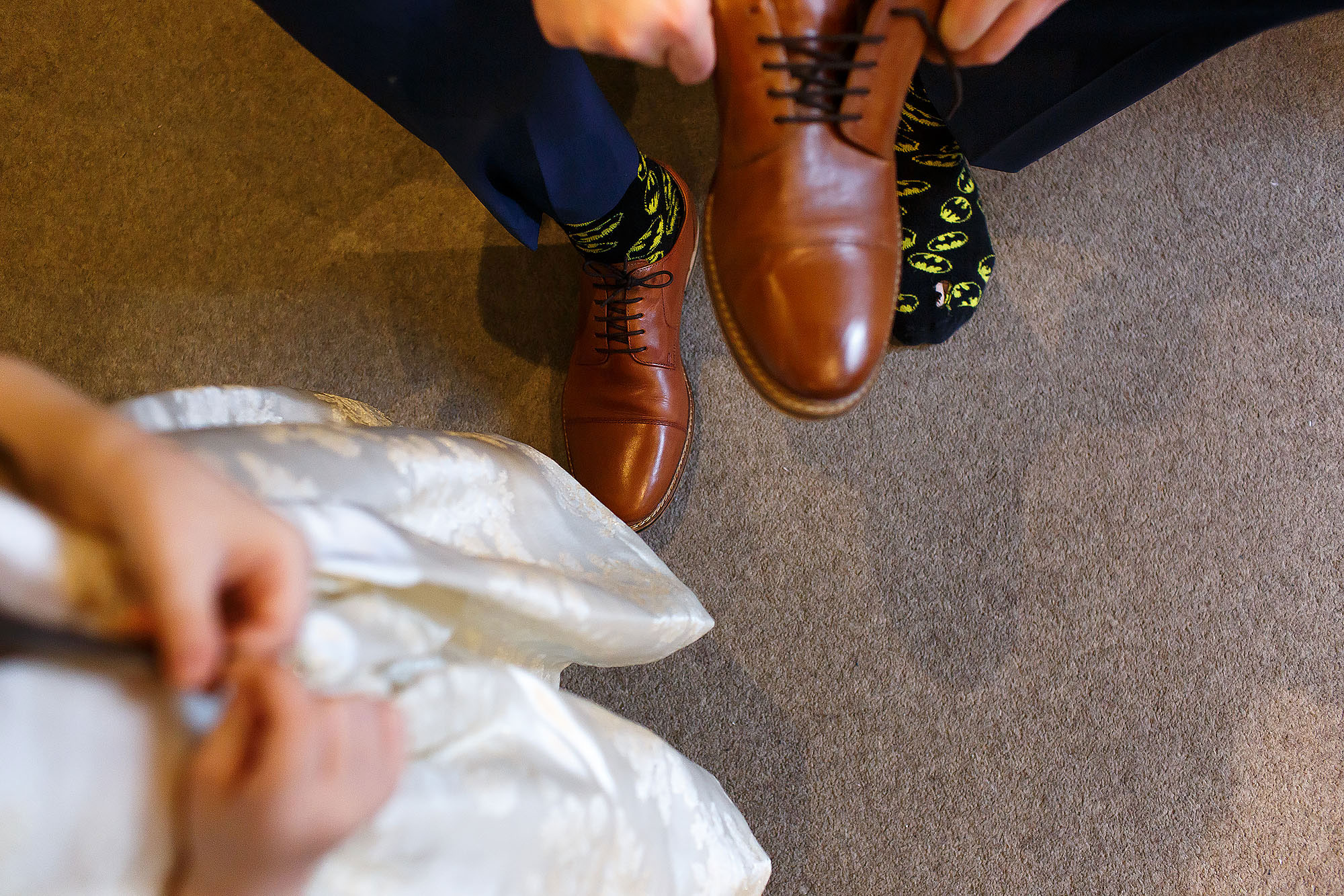 Flower girl fastening shoes as Groom puts on his batman socks | Mitton Hall wedding photographs by Toni Darcy Photography