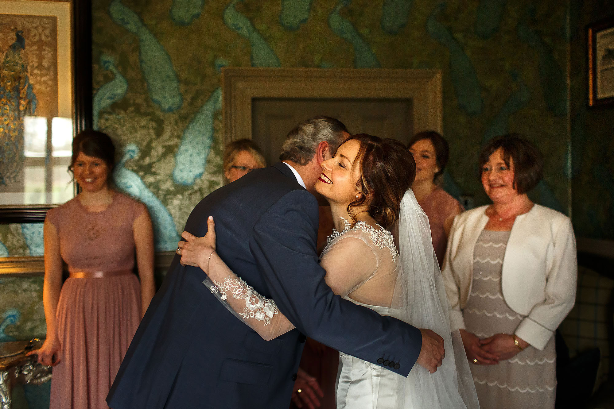 Father of the bride hugging the bride wearing long sleeved dress and veil as the bridesmaids wearing pink watch | Mitton Hall wedding photographs by Toni Darcy Photography